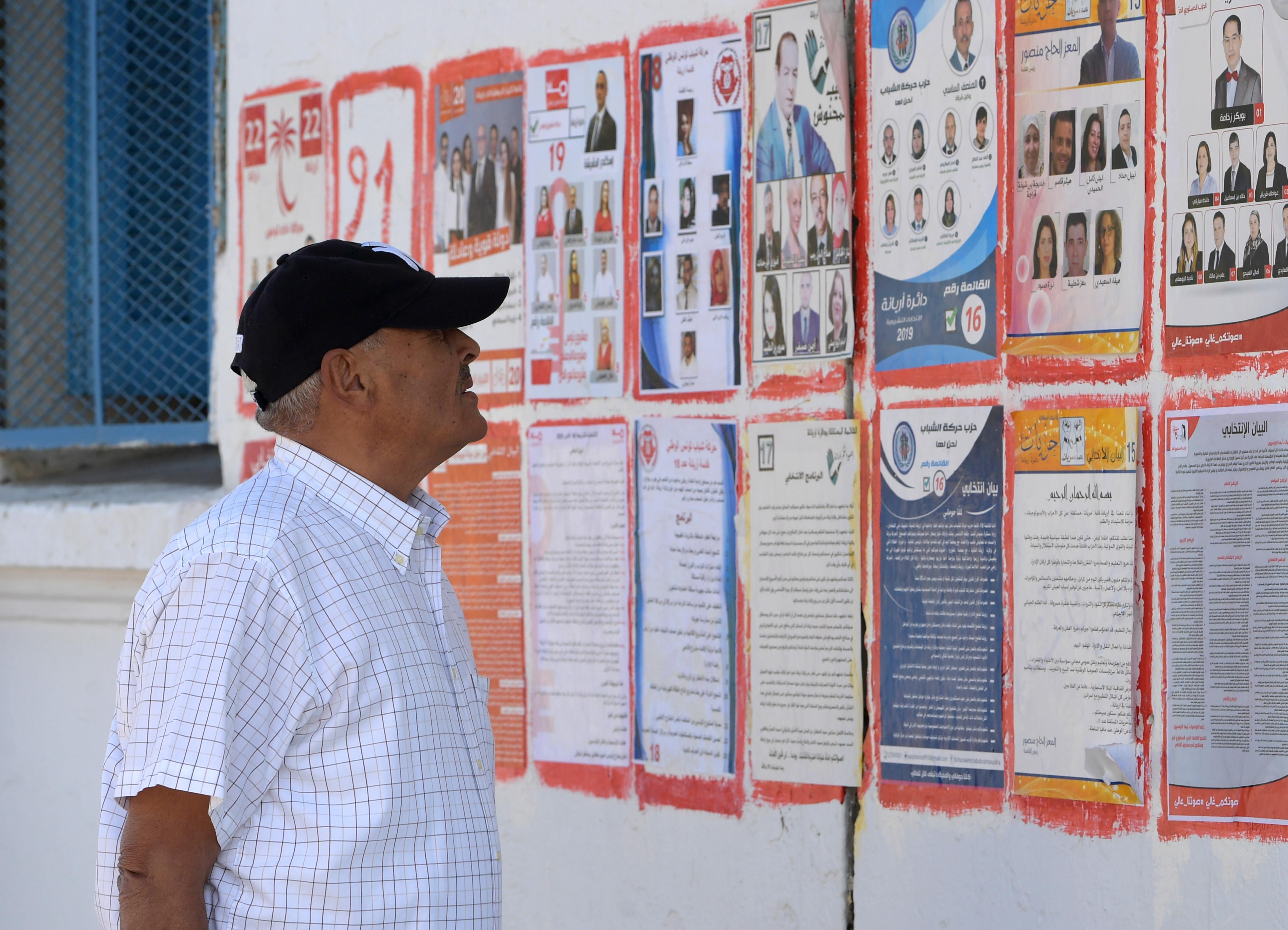 تونسي يتفحص دعايات ووعود المرشحين للانتخابات التشريعية
