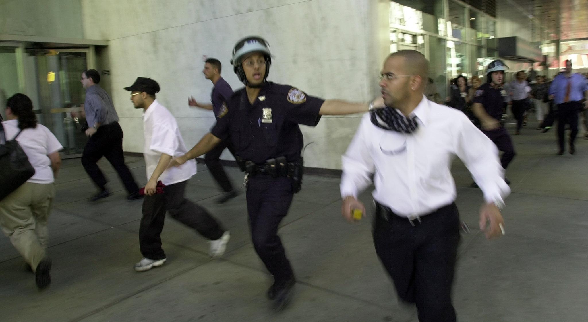 أشخاص يهربون إثر انهيار أحد البرجين
