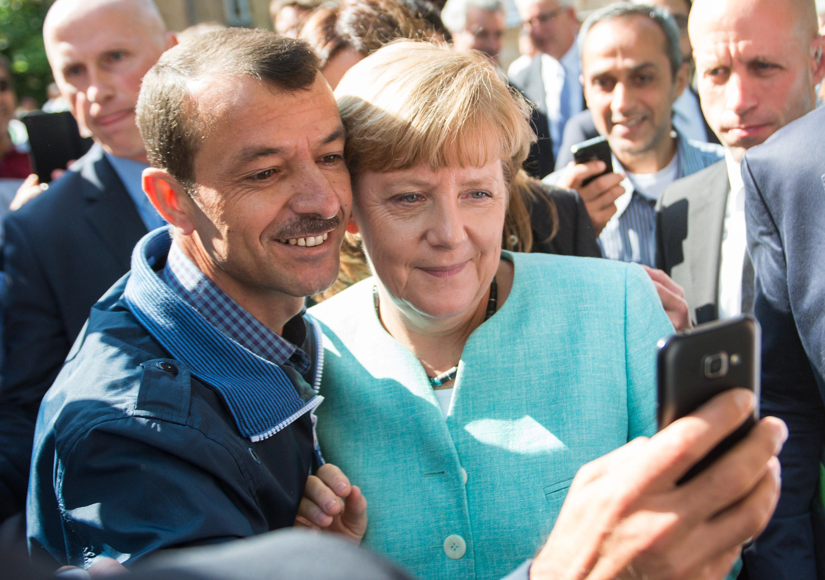 ميركل مع اللاجئين