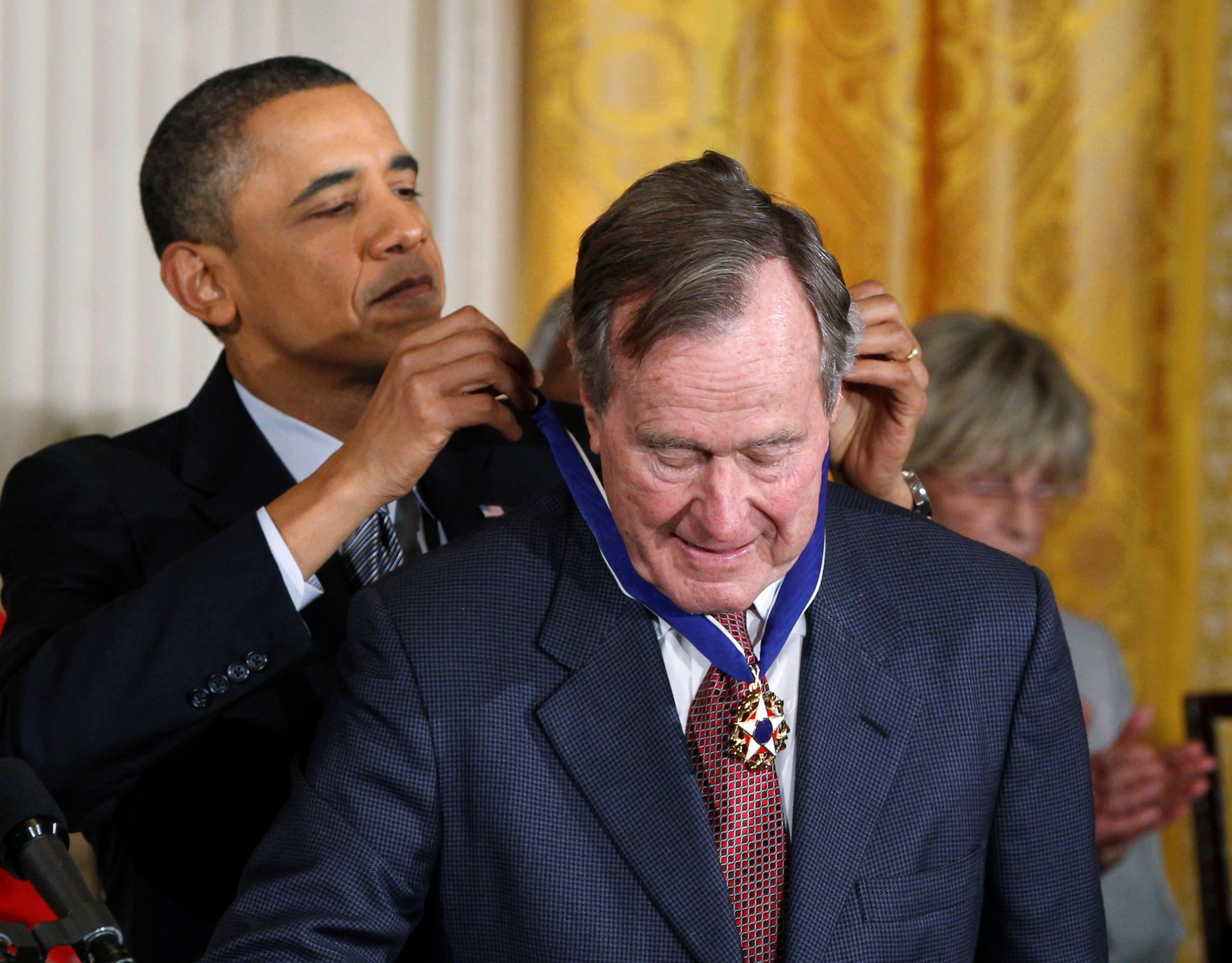 الرئيس السابق باراك أوباما يمنح الرئيس السابق جورج بوش الأب وسام الحرية خلال احتفال بالبيت الأبيض في فبراير 2011