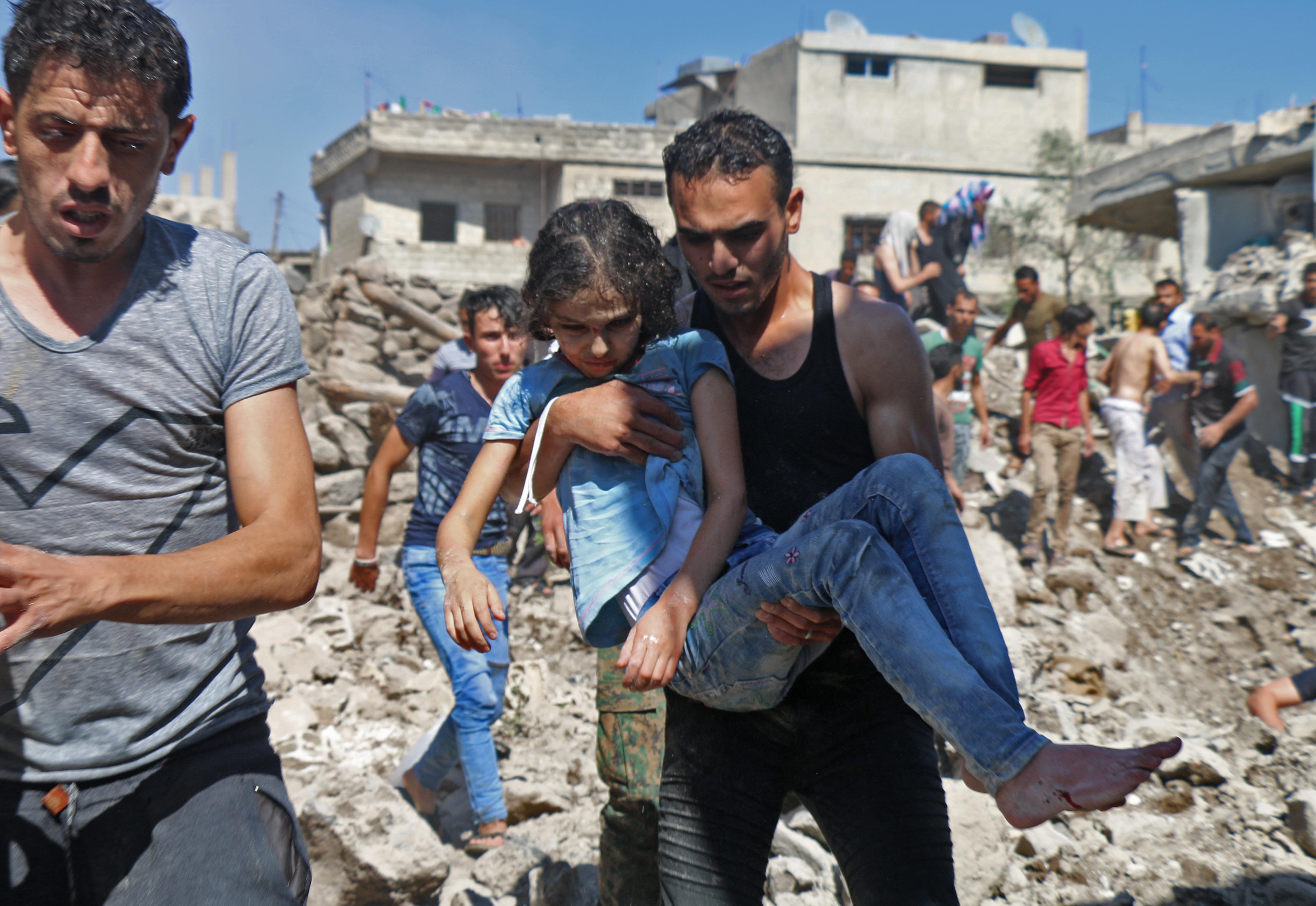 رجل يحمل طفلة في منطقة تعرضت لقصف روسي سوري قرب درعا
