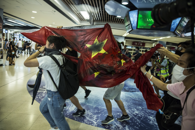 متظاهرون يحملون العلم الوطني الصيني بعد إنزاله من مجمع تجاري في حي شا تين