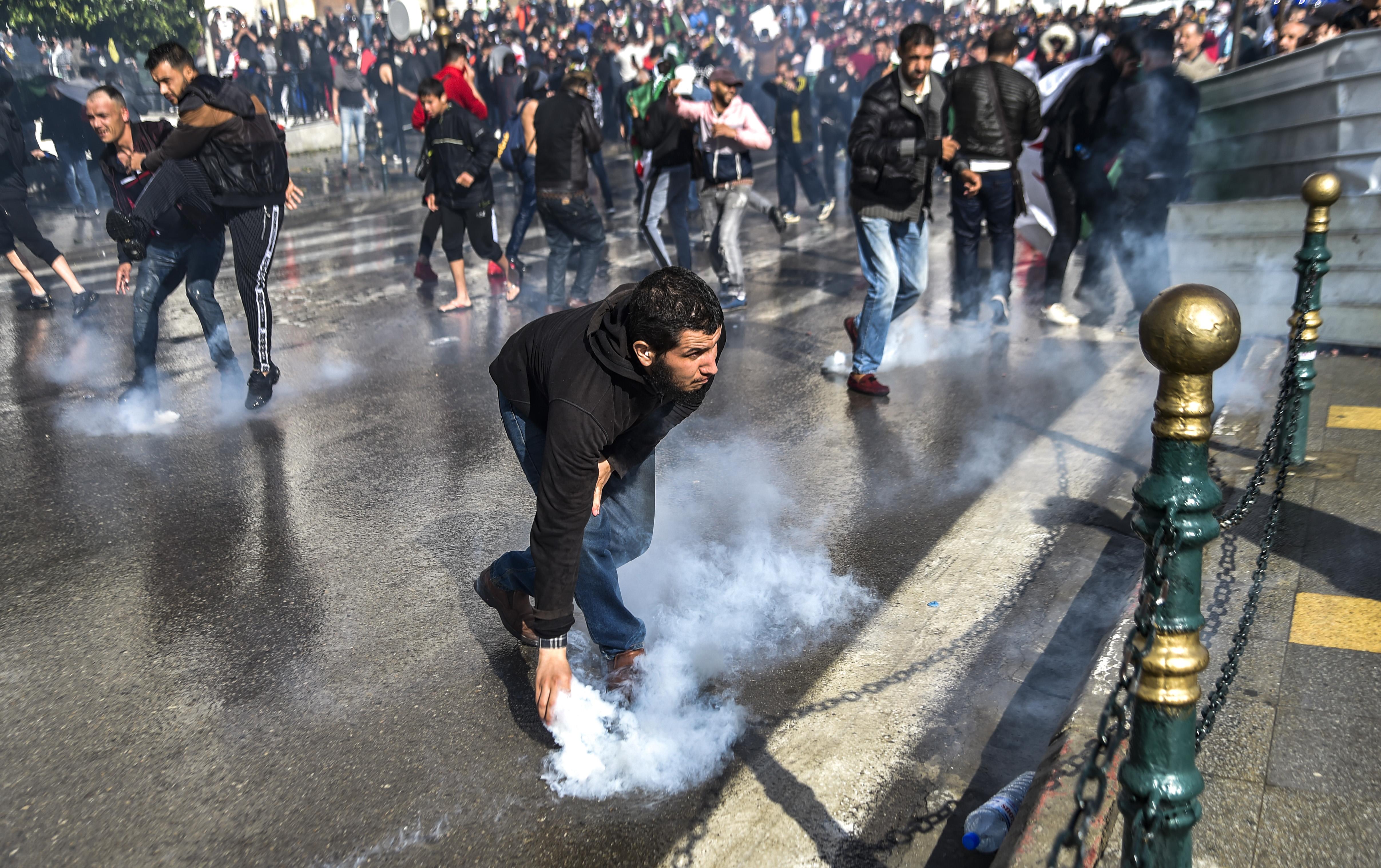 متظاهر جزائري يلتقط قنبلة غاز مسيلة للدموع خلال اشتباكات مع الأمن في العاصمة