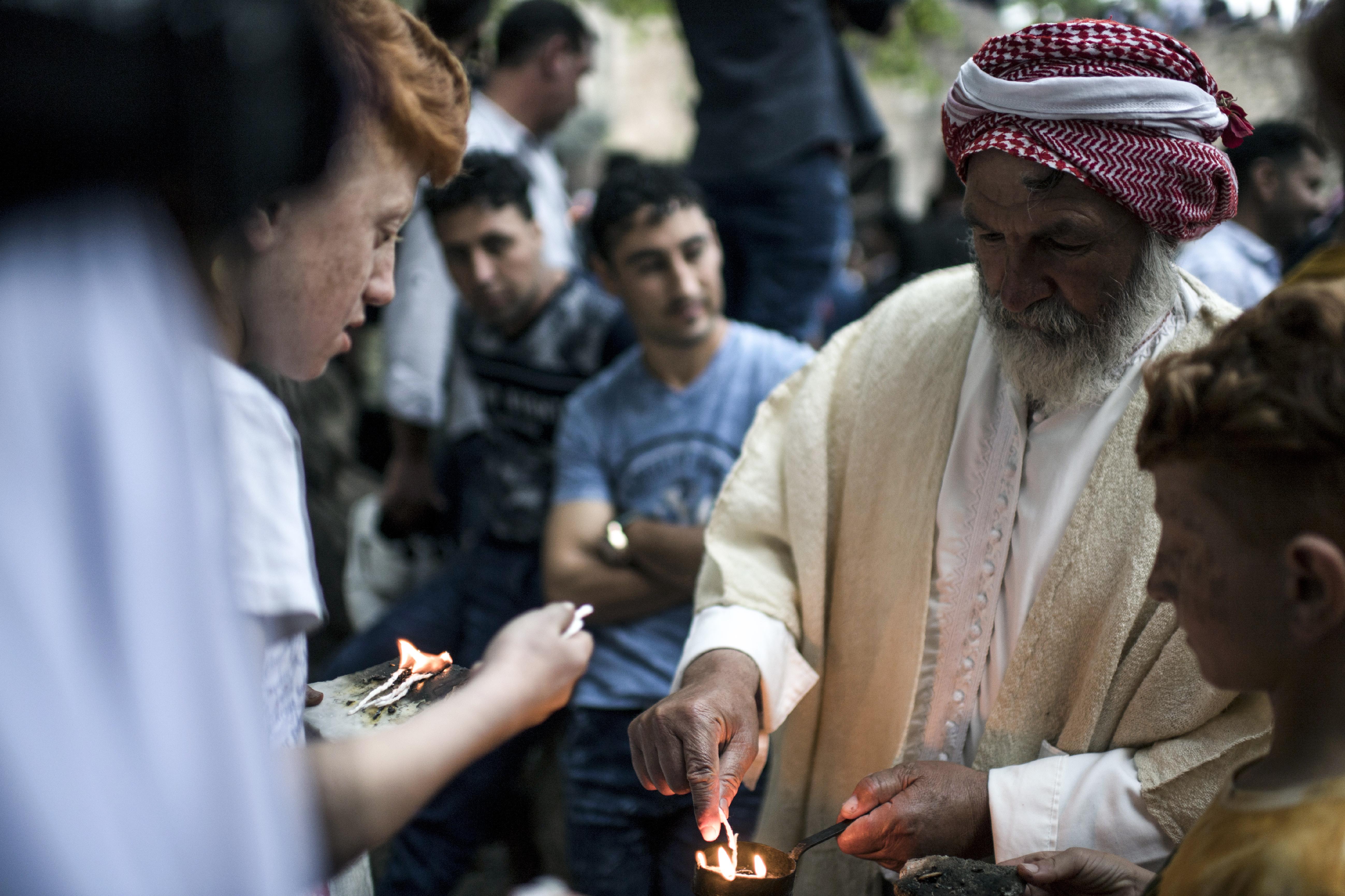 رجل أيزيدي يشعل الشمع في لالش خلال الاحتفال برأس السنة