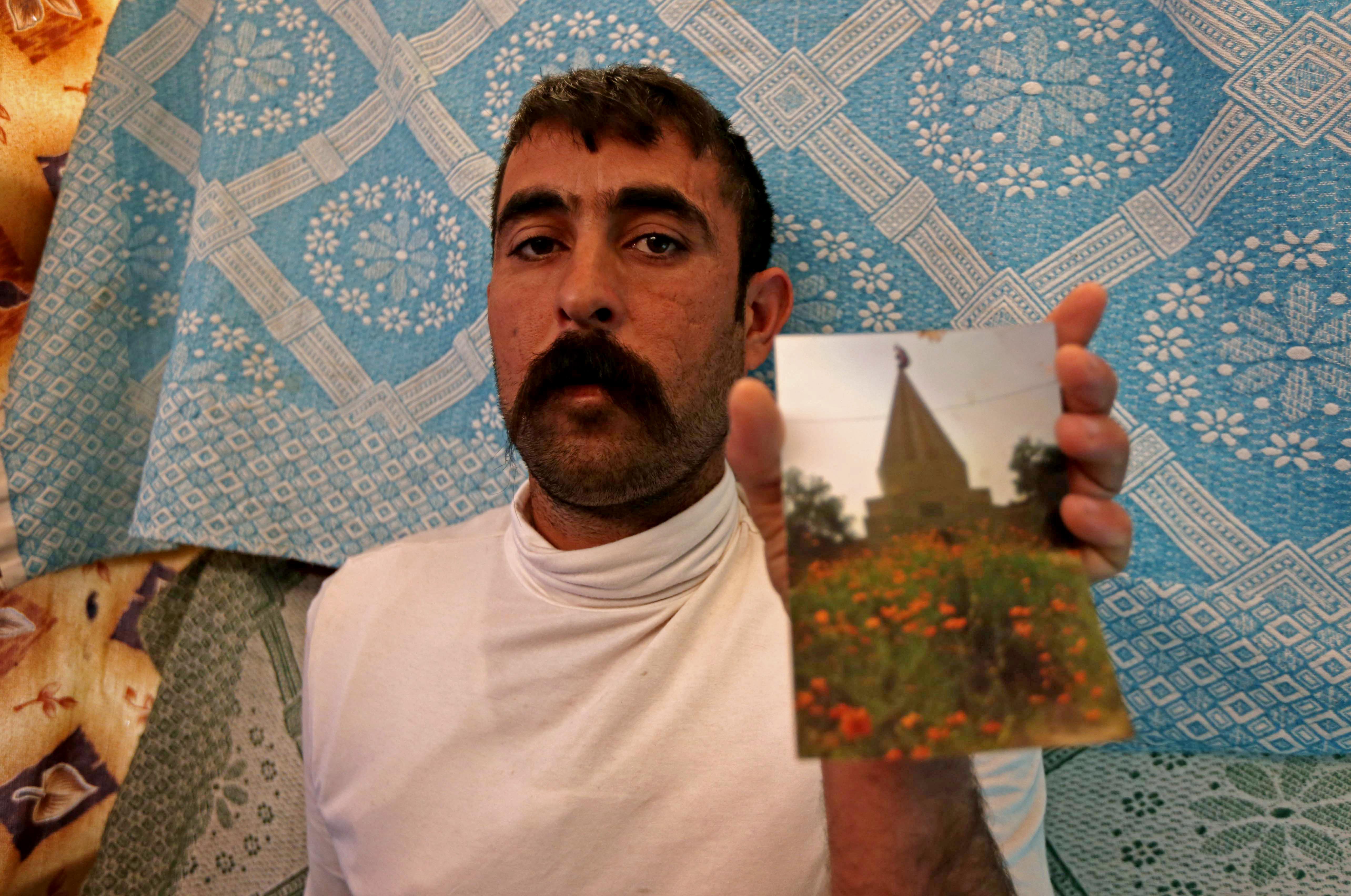 علي محمود نازح أيزيدي وبيده صورة لمعبد لالش