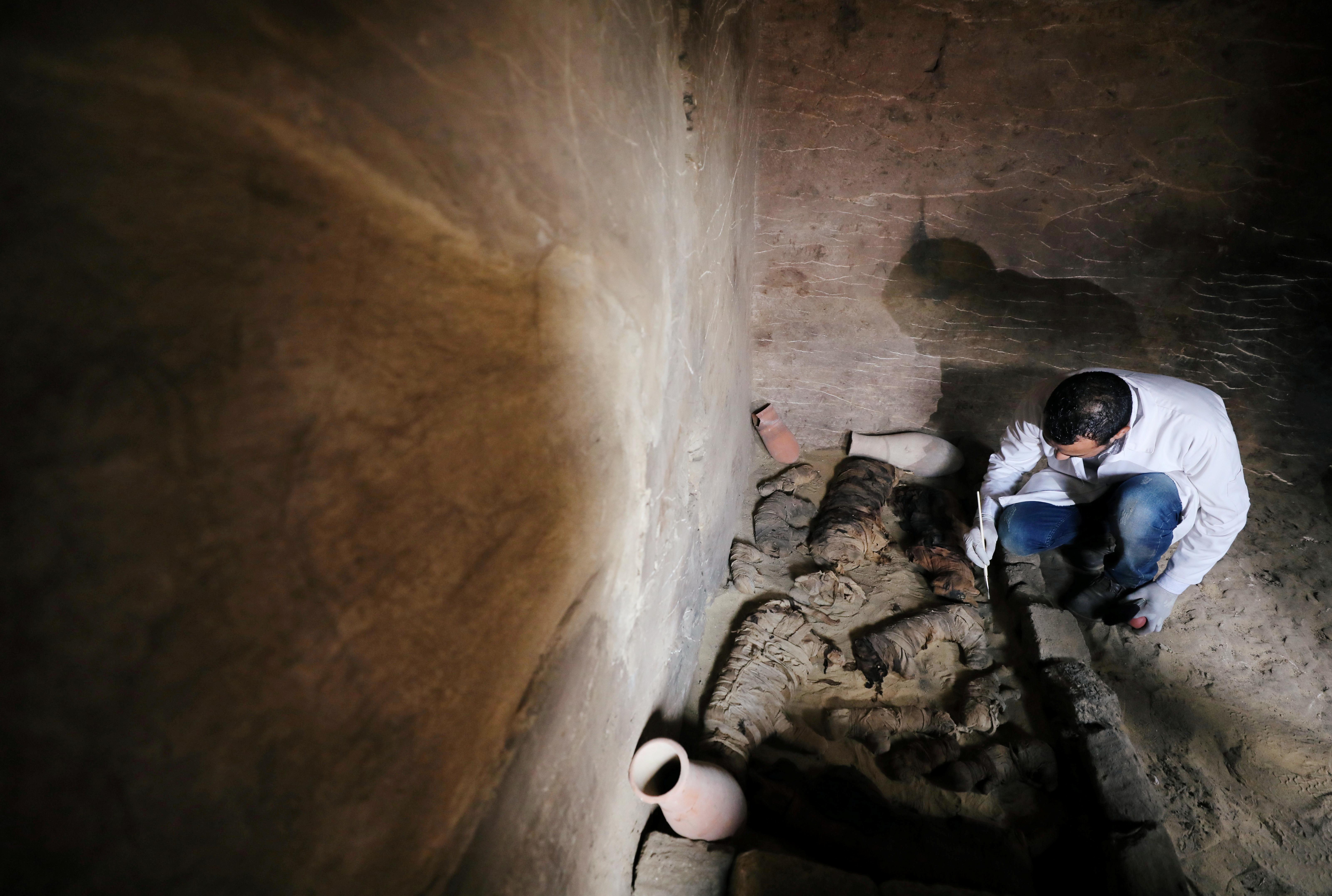 عالم آثار يعاين القطع المكتشفة داخل المقبرة