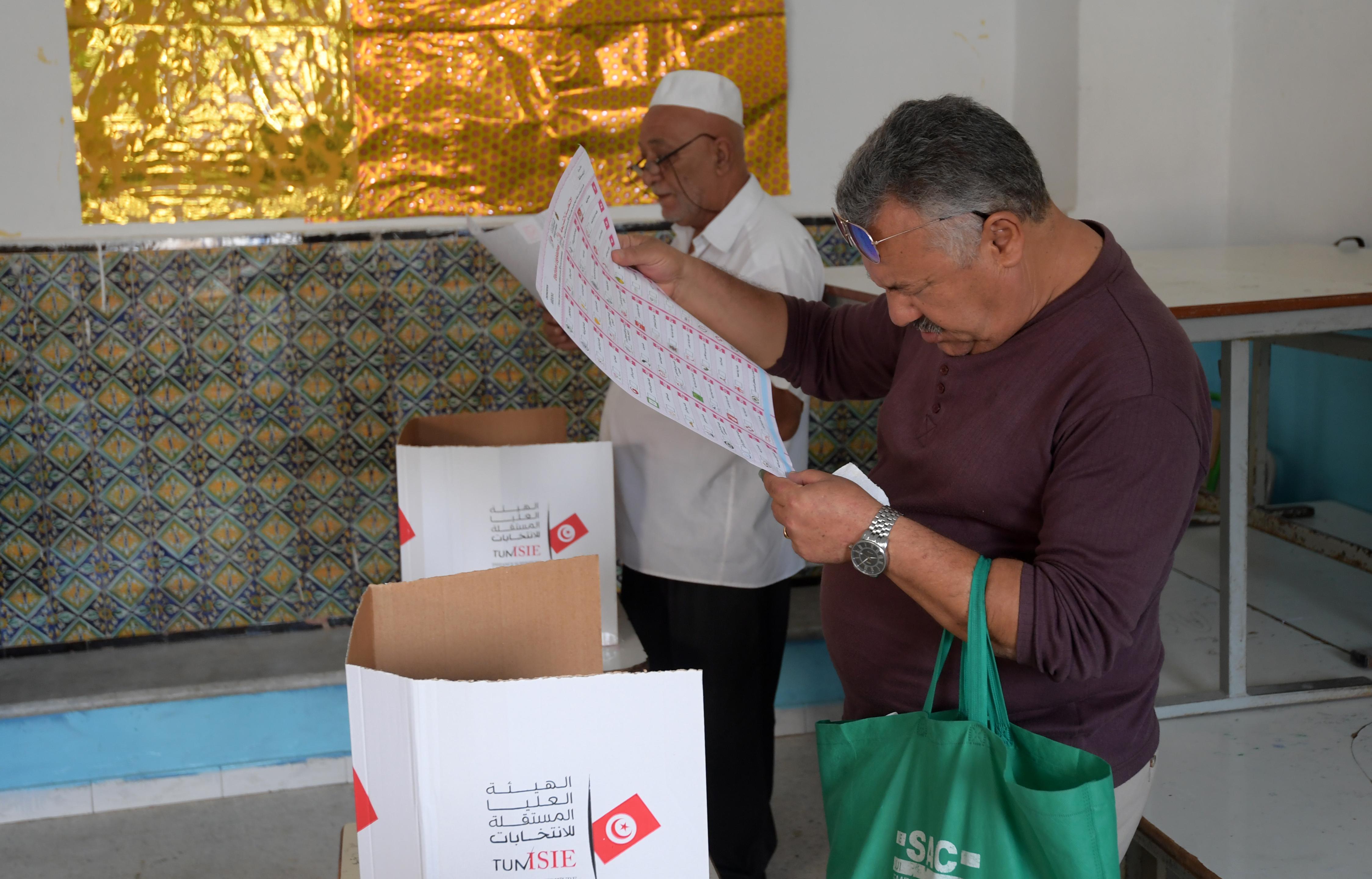 تونسي يتفحص قائمة المرشحين استعدادا للإدلاء بصوته في الانتخابات