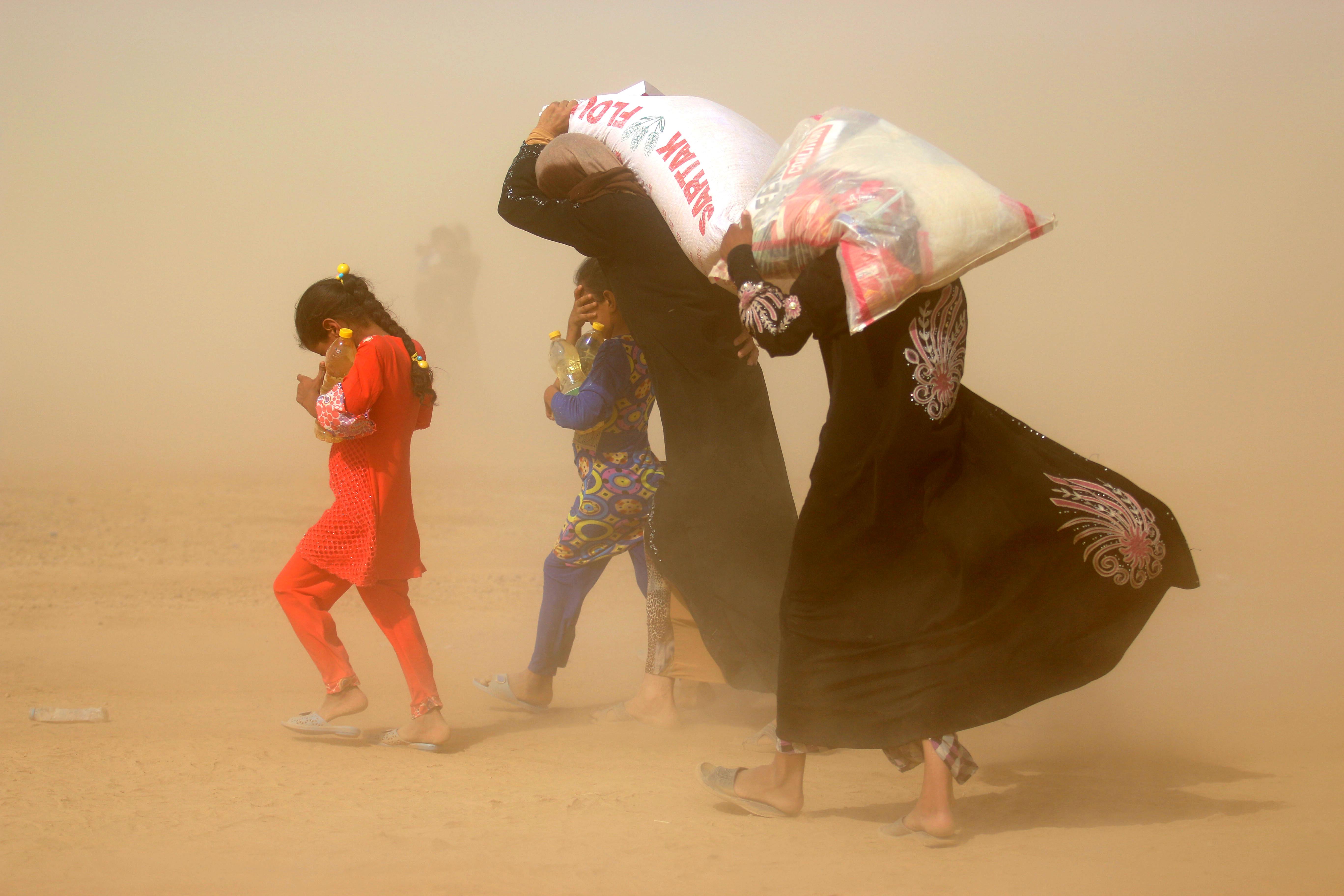 نازحون من الفلوجة يحملون مساعدات غذائية في مخيم في الخالدية