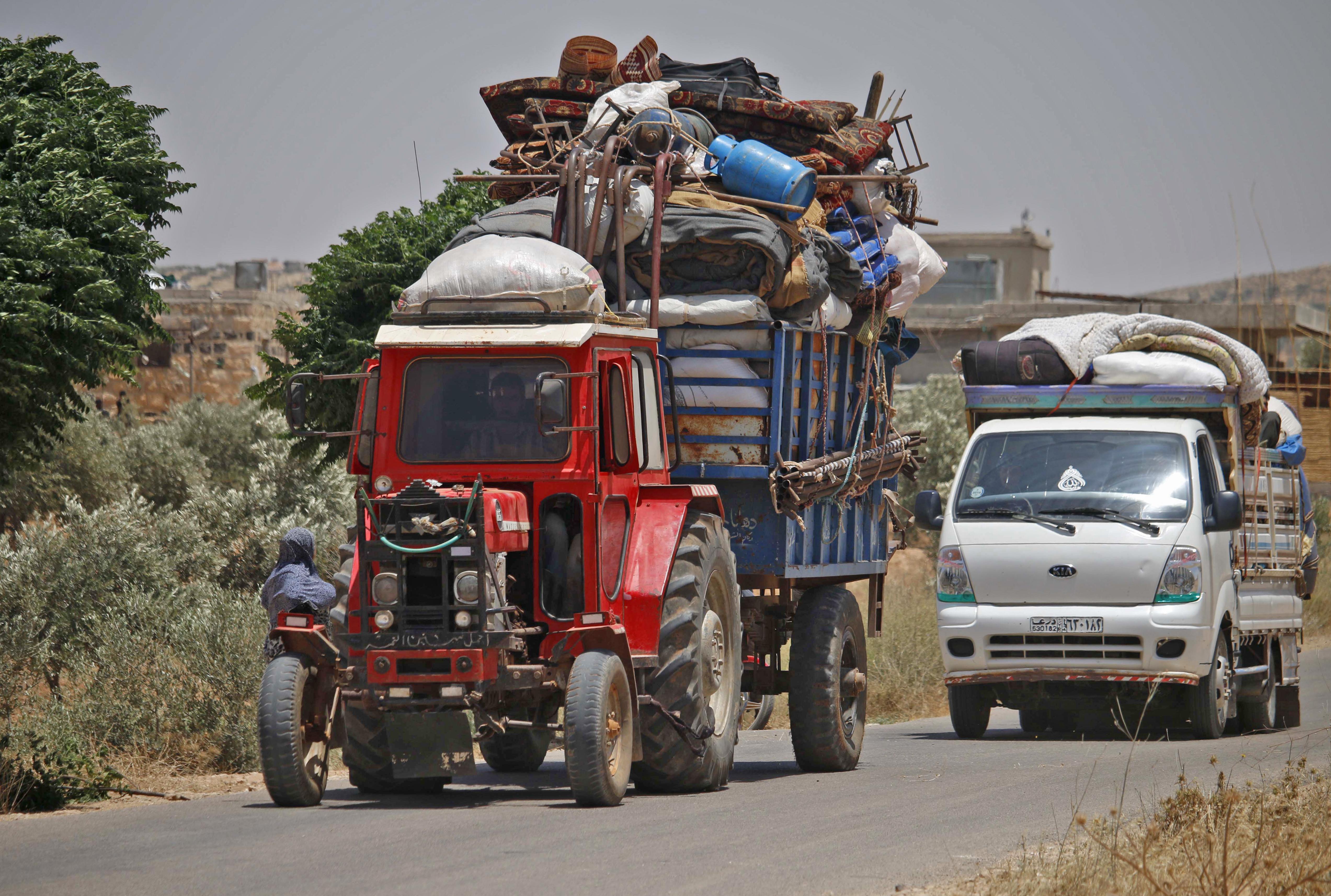 نازحون يستقلون جرارا زراعيا وشاحنة هربا من مناطق القتال في جنوب غرب سورية.