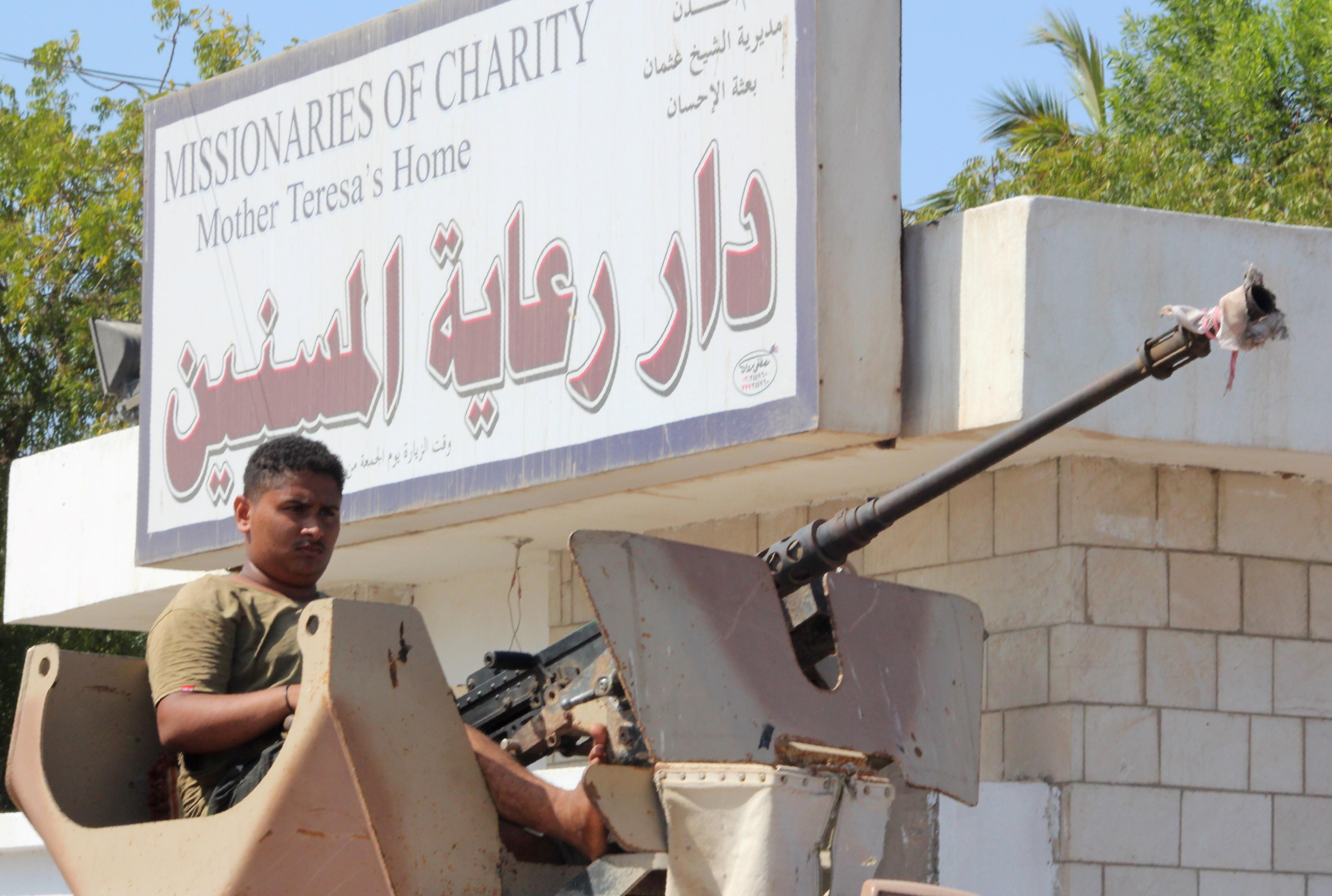 مقاتلون موالون للحكومة اليمنية أمام مركز لرعاية المسنين في عدن بعد تعرضه للهجوم