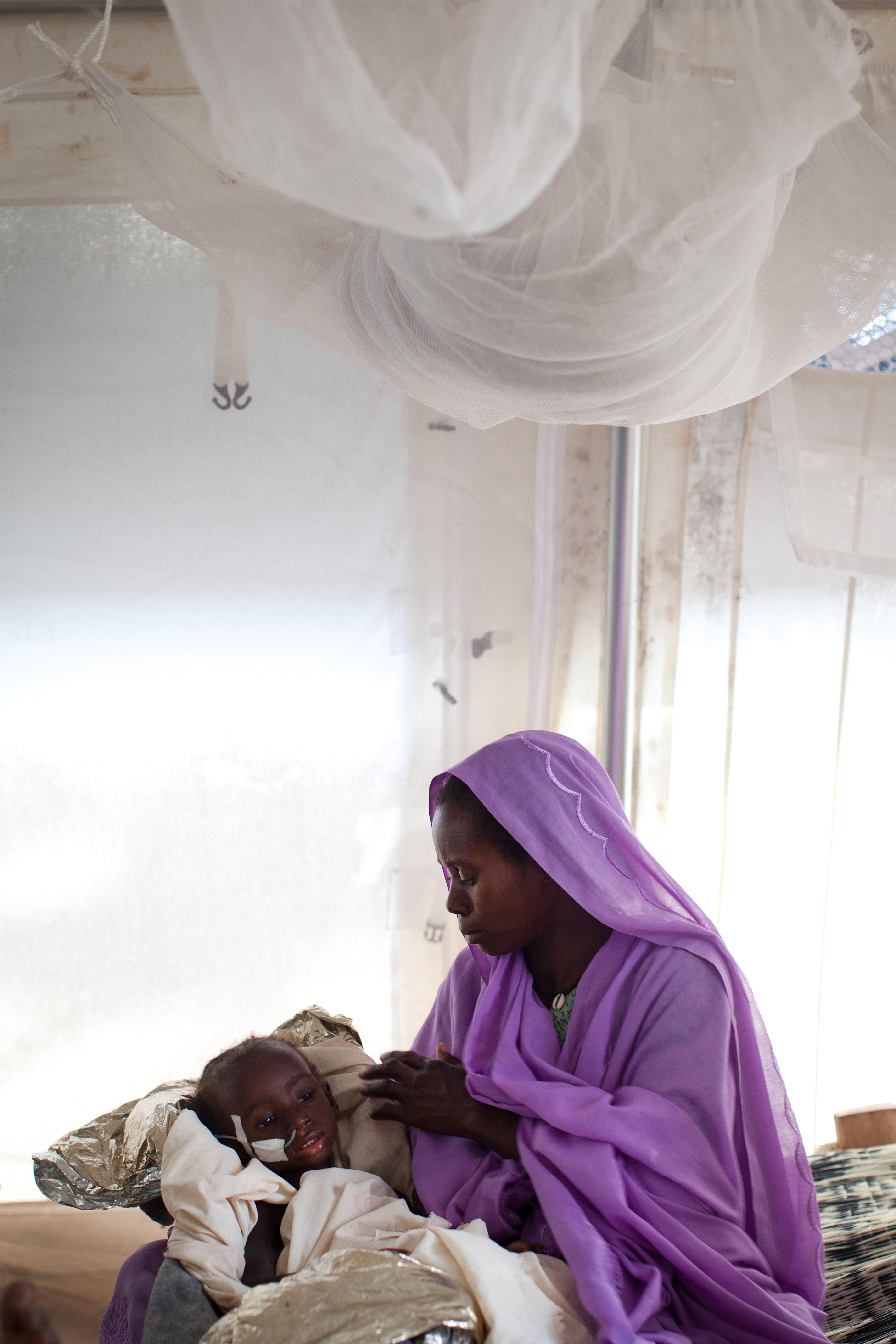 أم تراعي ابنتها المريضة في مستشفى بالسودان
