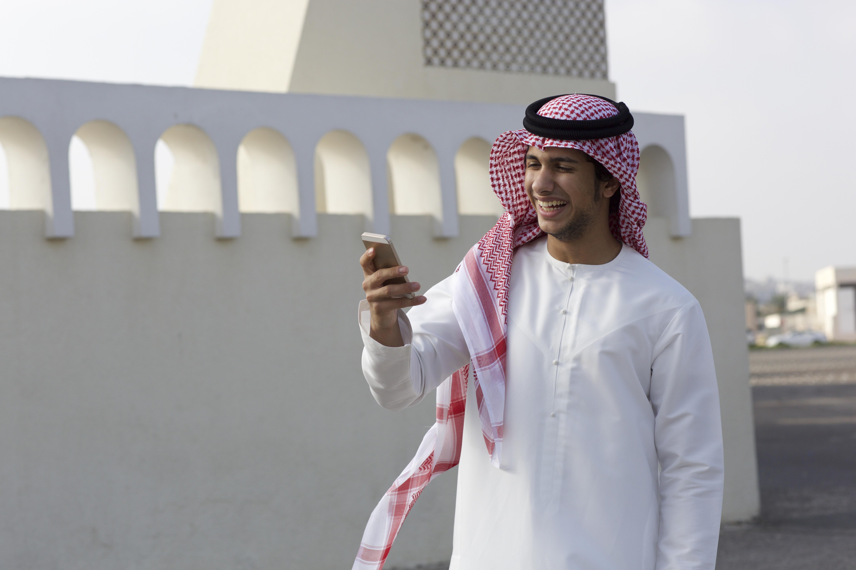 شاب يستخدم هاتفه في دبي