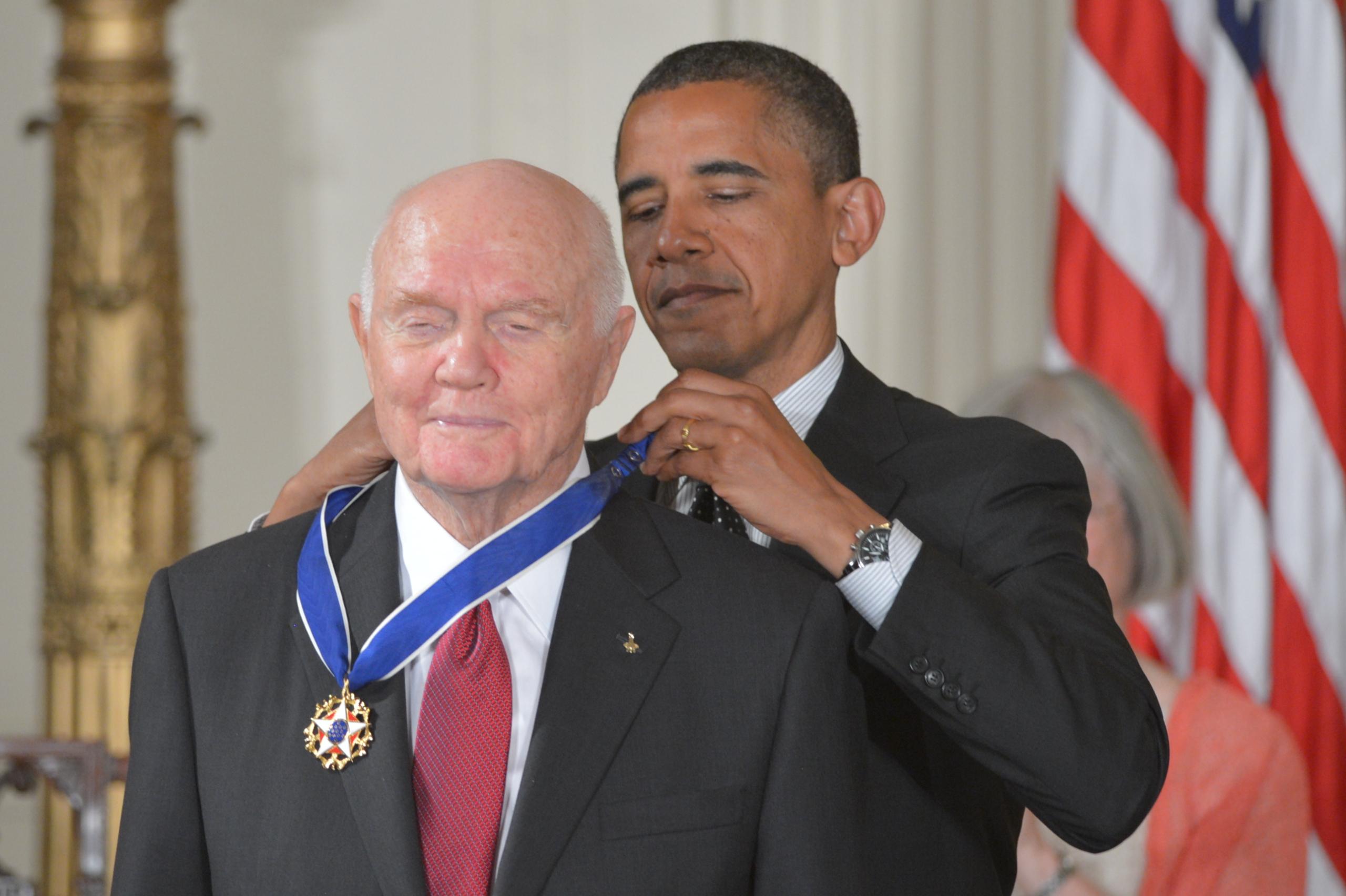 الرئيس باراك أوباما وهو يقلد جون غلين وسام الحرية الرئاسي عام 2012