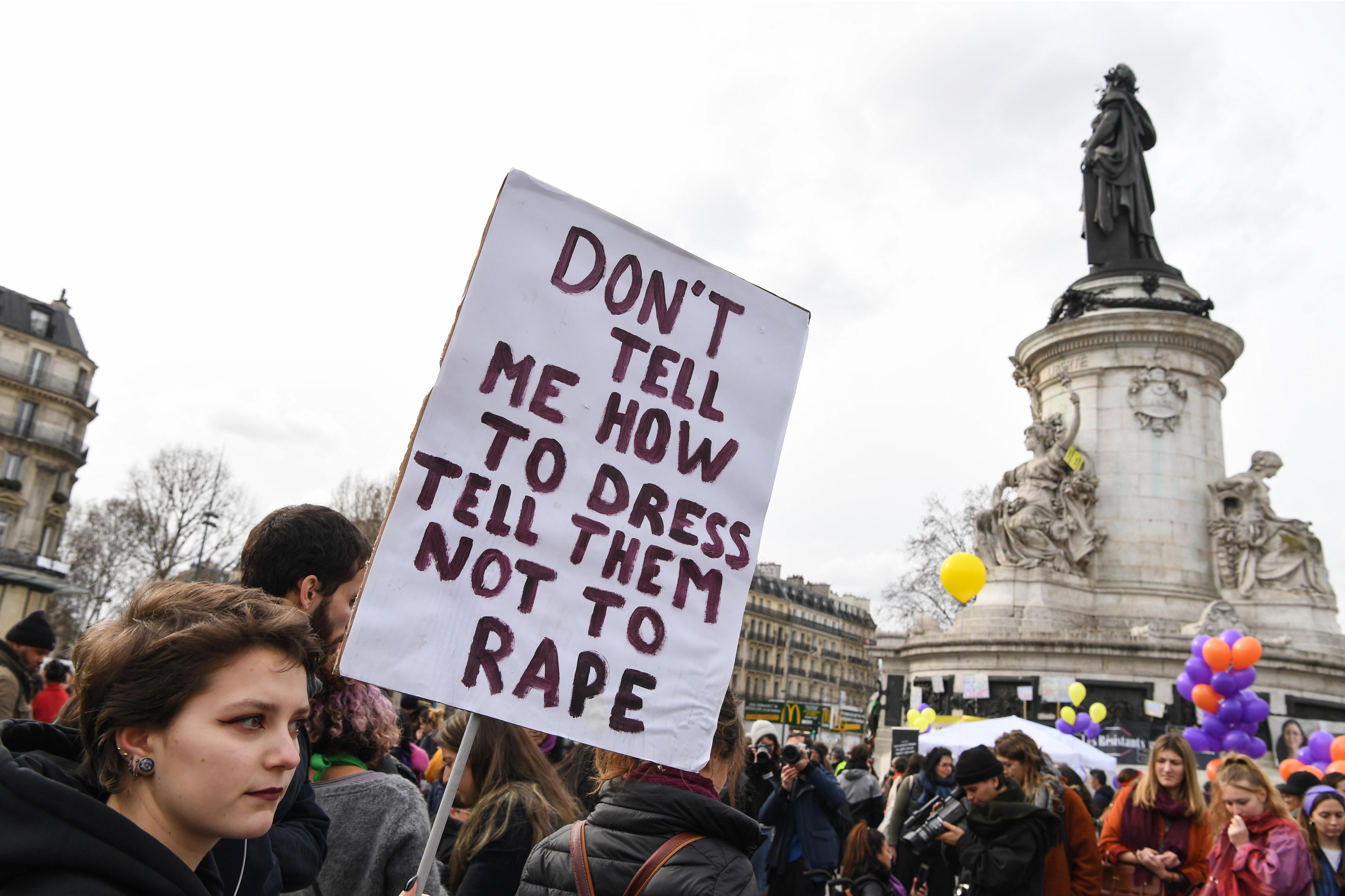 """سيدة ترفع لافتة تقول """"لا تقل لي ماذا ألبس، قل لهم ألا يغتصبوا"""""""