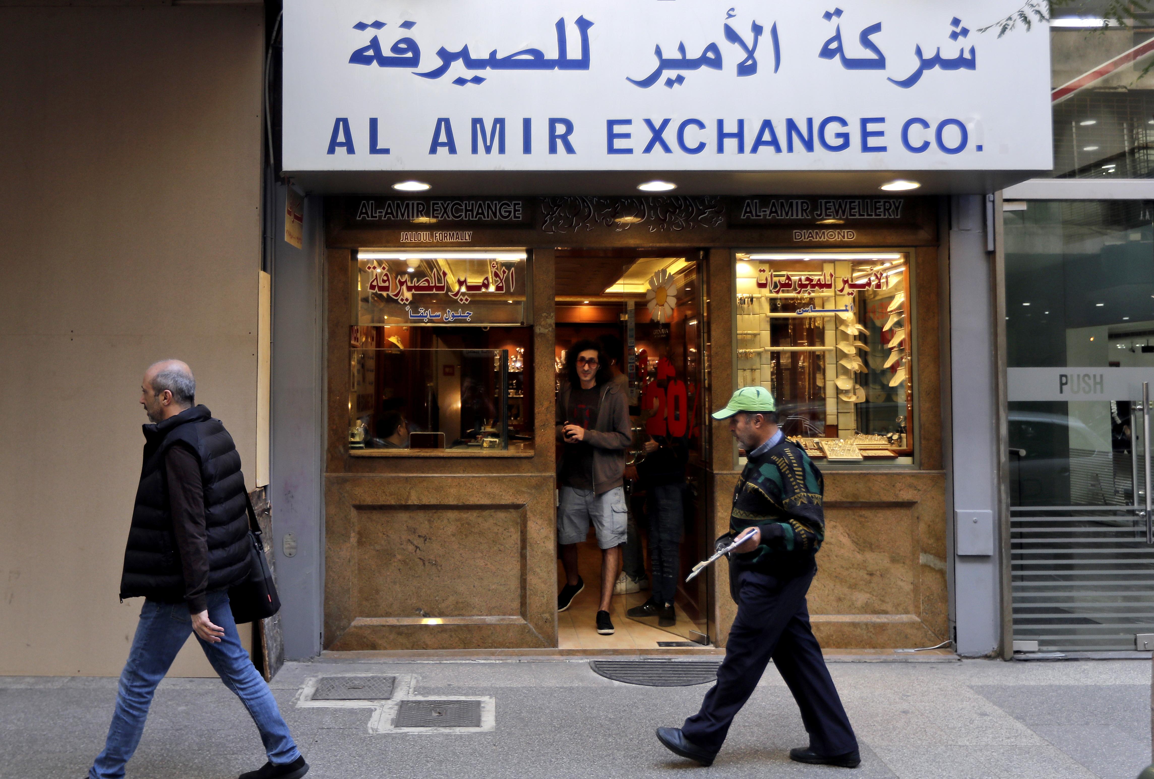 لبنانيون يمرون أمام صرافة مغلقة في بيروت