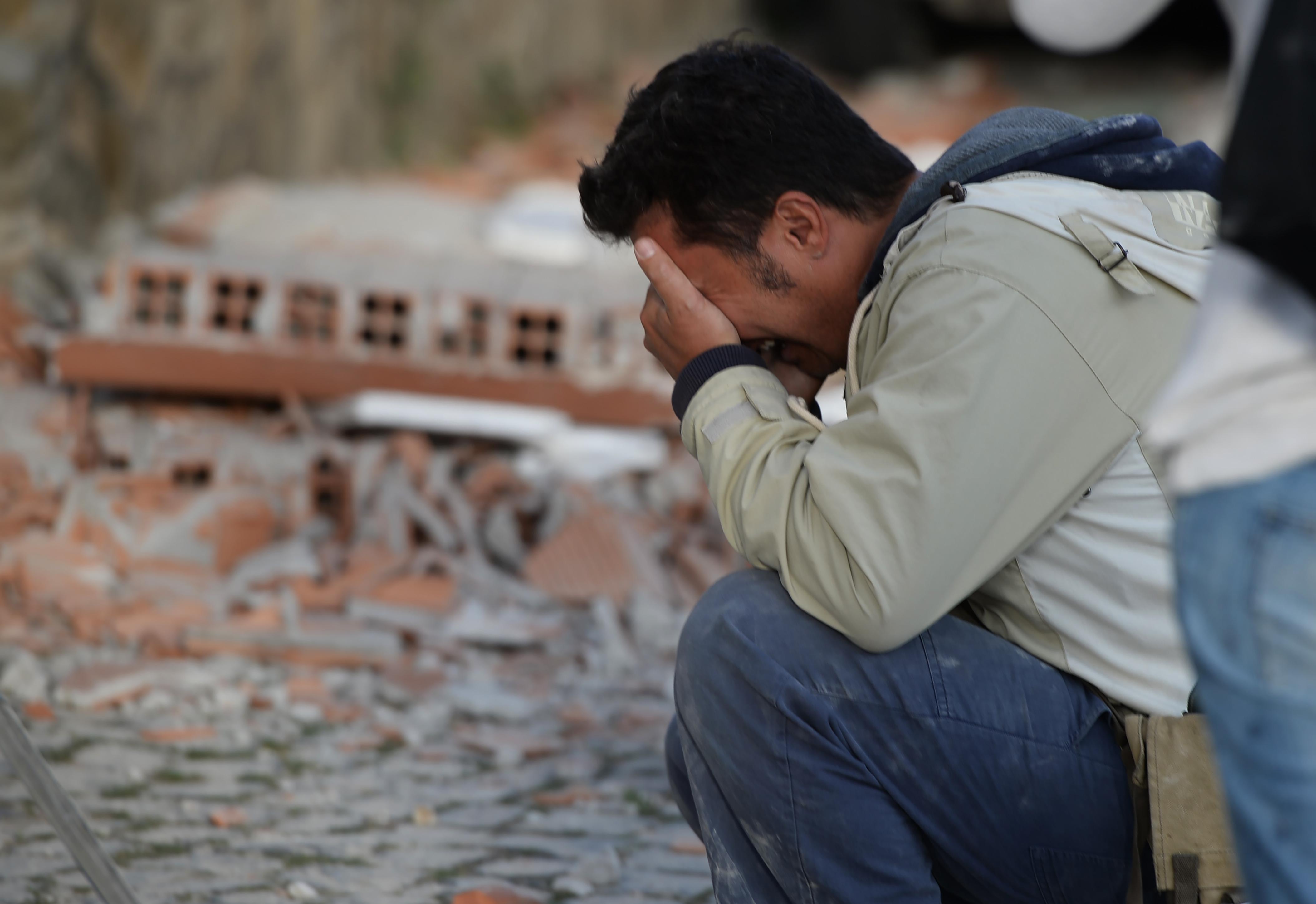 رجل يذرف الدموع بعد الزلزال