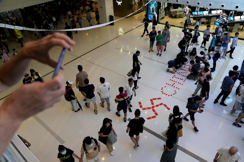 محتجون يرسمون الصليب المعقوف إلى جوار اسم الصين في مجمع تجاري في منطقة شا تن في هونغ كونغ