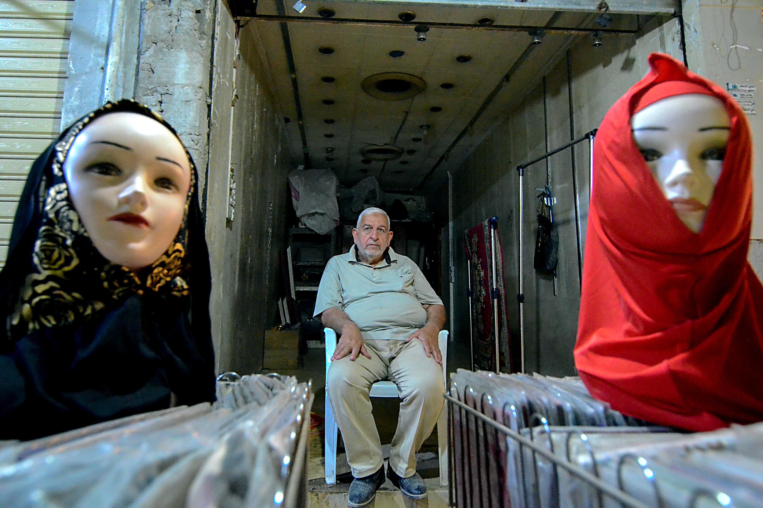 تاجر عراقي يبيع أغطية الرأس في الموصل