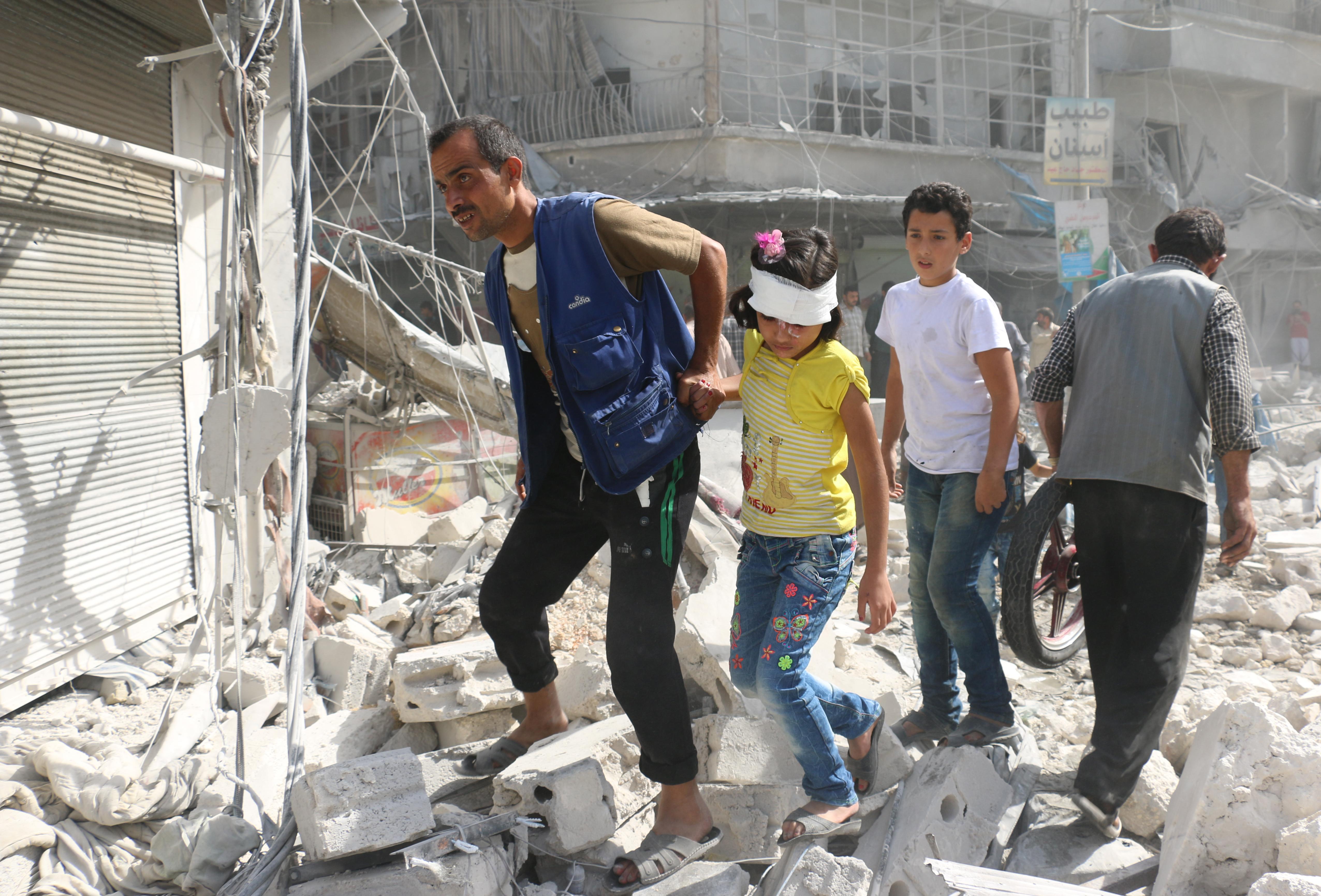 سوريون في إحدى مناطق حي الفردوس بعد تعرضه لغارة جوية في 12 أكتوبر