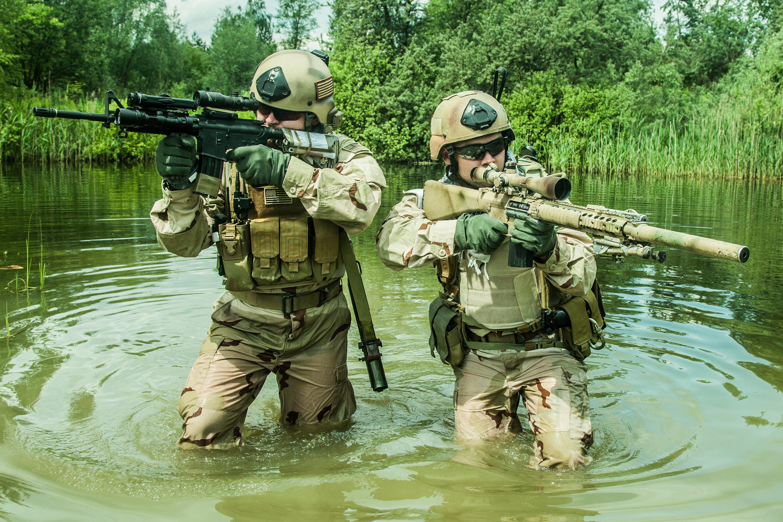 عنصران من القوة يقطعان نهرا بأسلحتهما