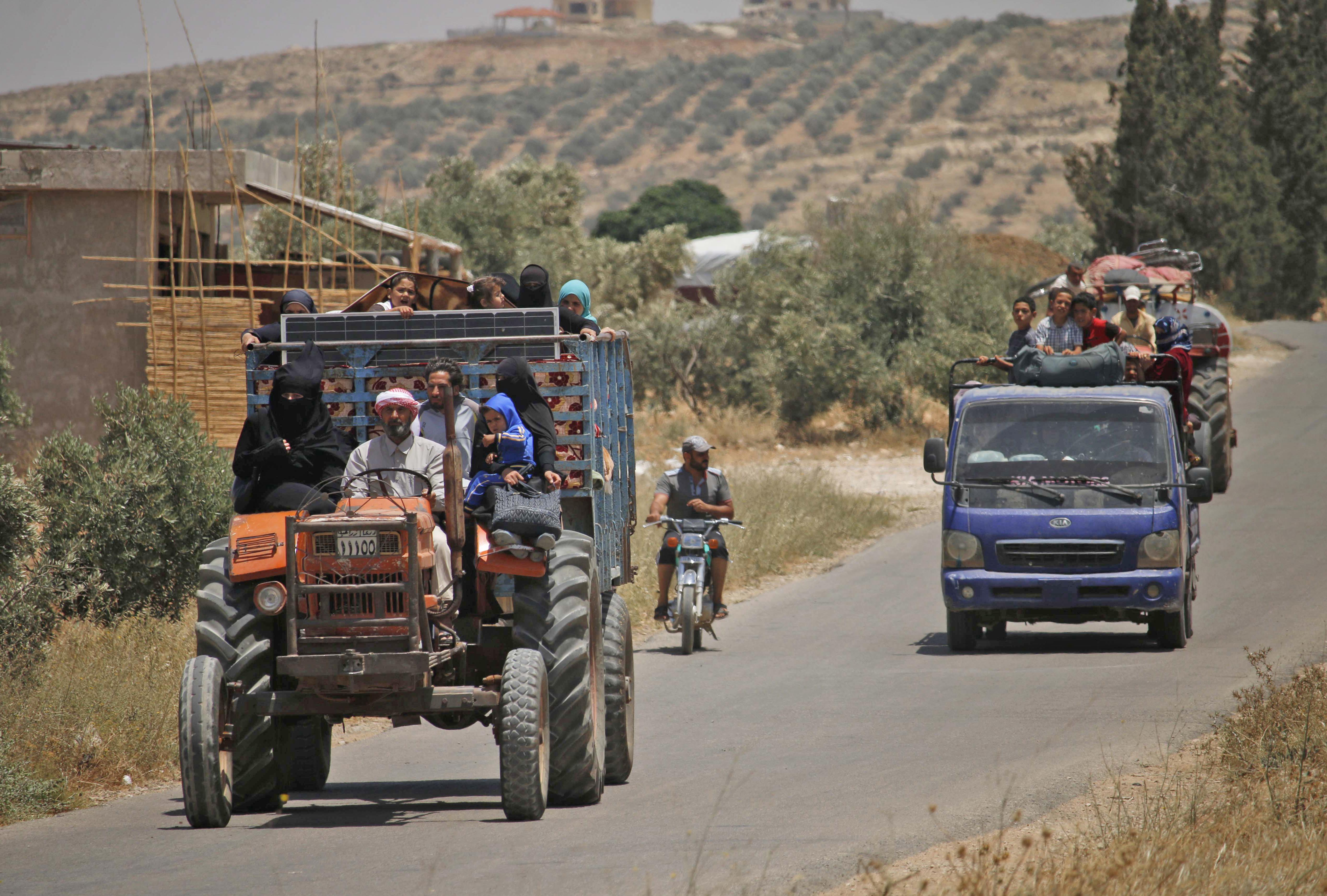 سوريون يستقلون جرارا زراعيا وآخرون يستقلون شاحنة هربا من مناطق القصف في جنوب غرب البلاد