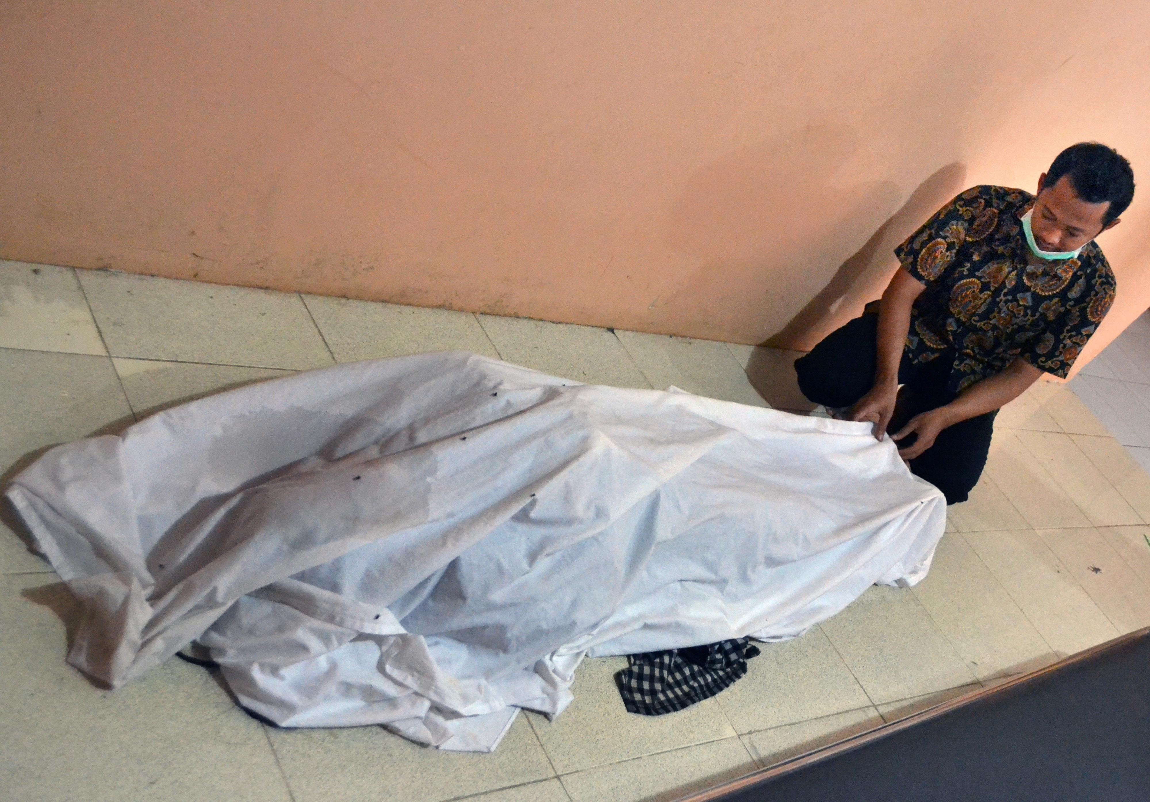 مواطن يجلس بالقرب من جثة أحد المتوفين بسبب تسونامي