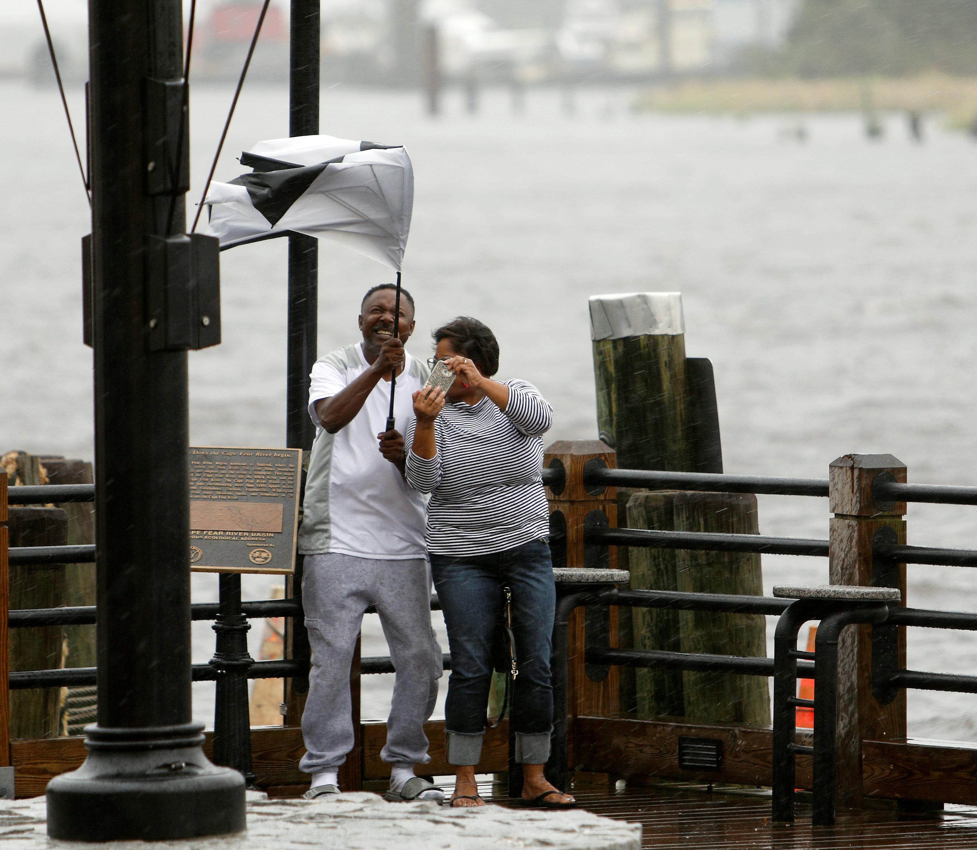 رجل وامرأة يحاولان التقاط صورة اثناء وصول الرياح القوية المرافقة لاعصار فلورنس