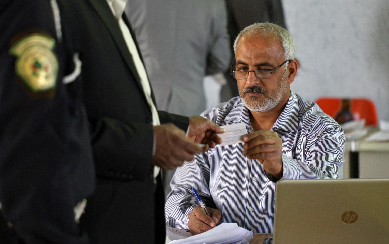 مسؤول في لجنة الانتخابات العراقية يتسلم بطاقة أحد الناخبين
