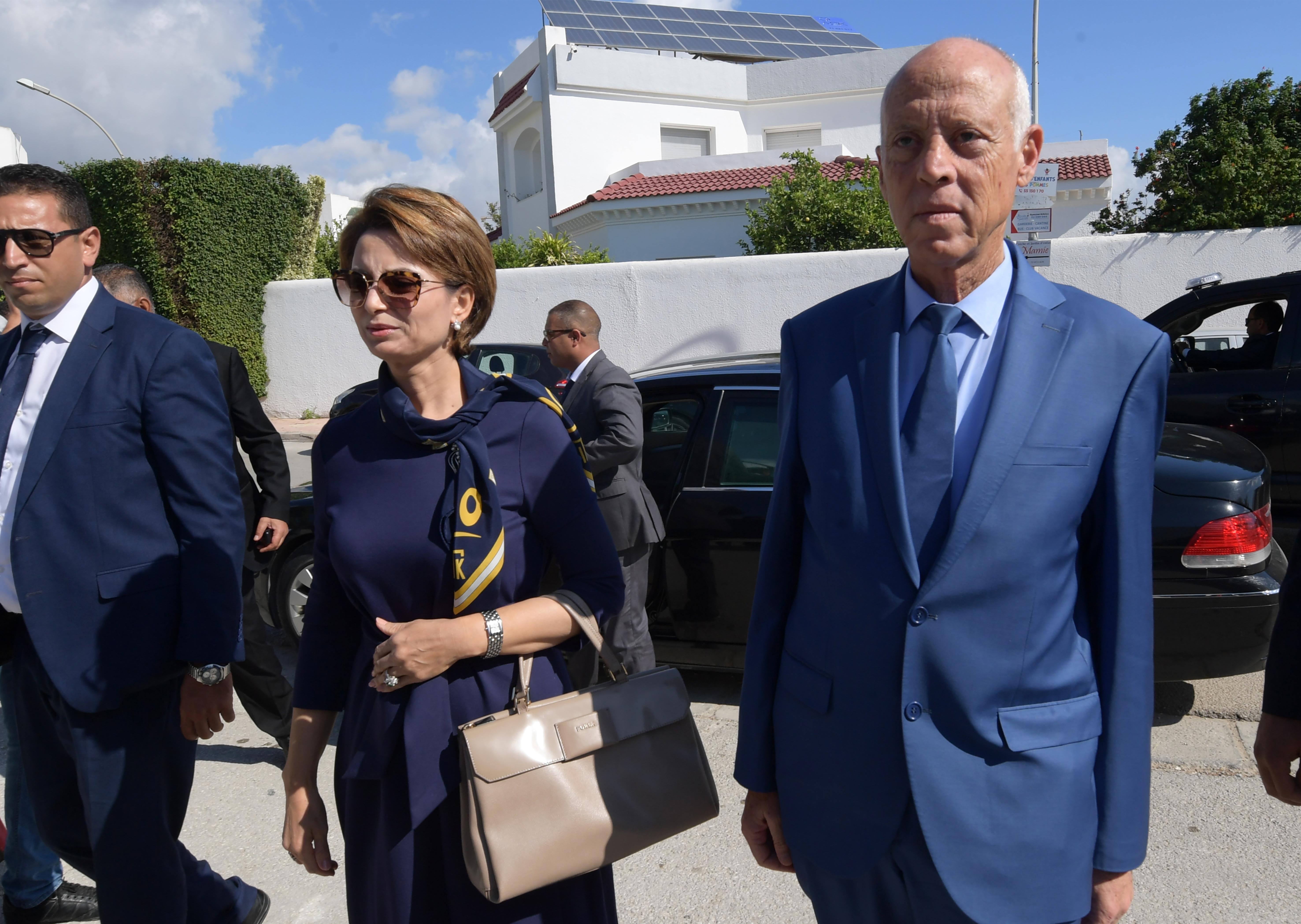 المرشح الرئاسي أستاذ القانون الدستوري وبجانبه زوجته أمام مقر لجنته الانتخابية