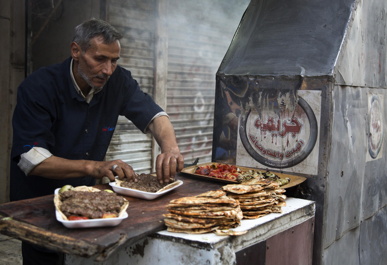 سوري يحضر وجبات الكباب ليبيعها للصائمين في شمال مدينة حلب