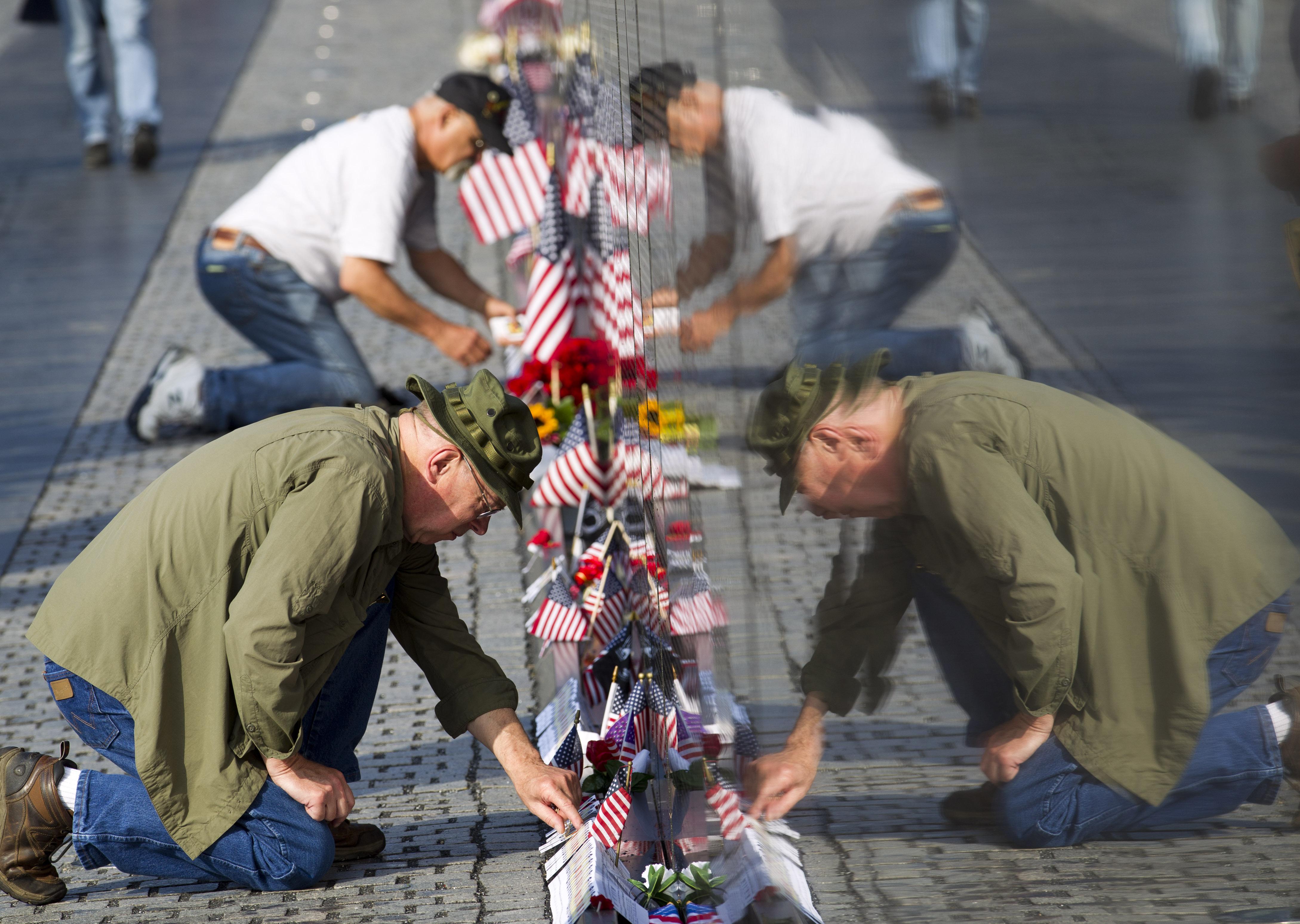 أميركيان في العاصمة واشنطن يضعان الأعلام أمام النصب التذكاري للمحاربين القدامى الذين شاركوا في حرب فيتنام