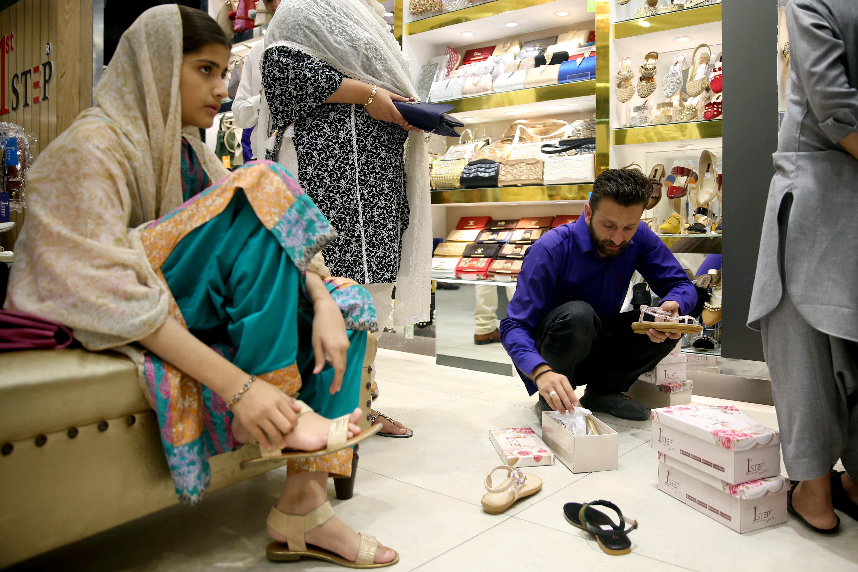 امرأة تقيس حذاء في احد محلات اسلام اباد في الباكستان