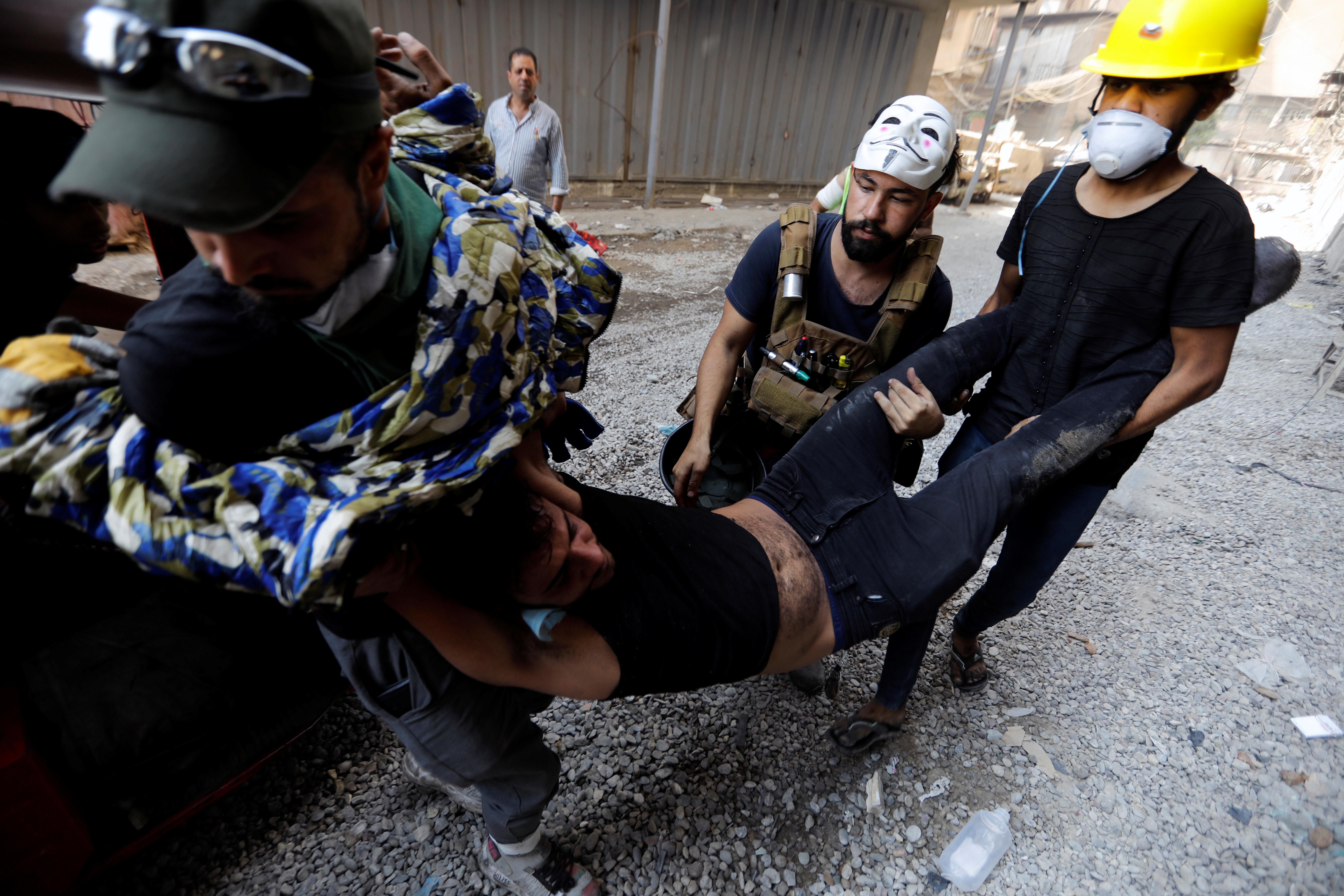 متظاهرون يساعدون أحد المصابين خلال الاحتجاجات المستمرة في بغداد