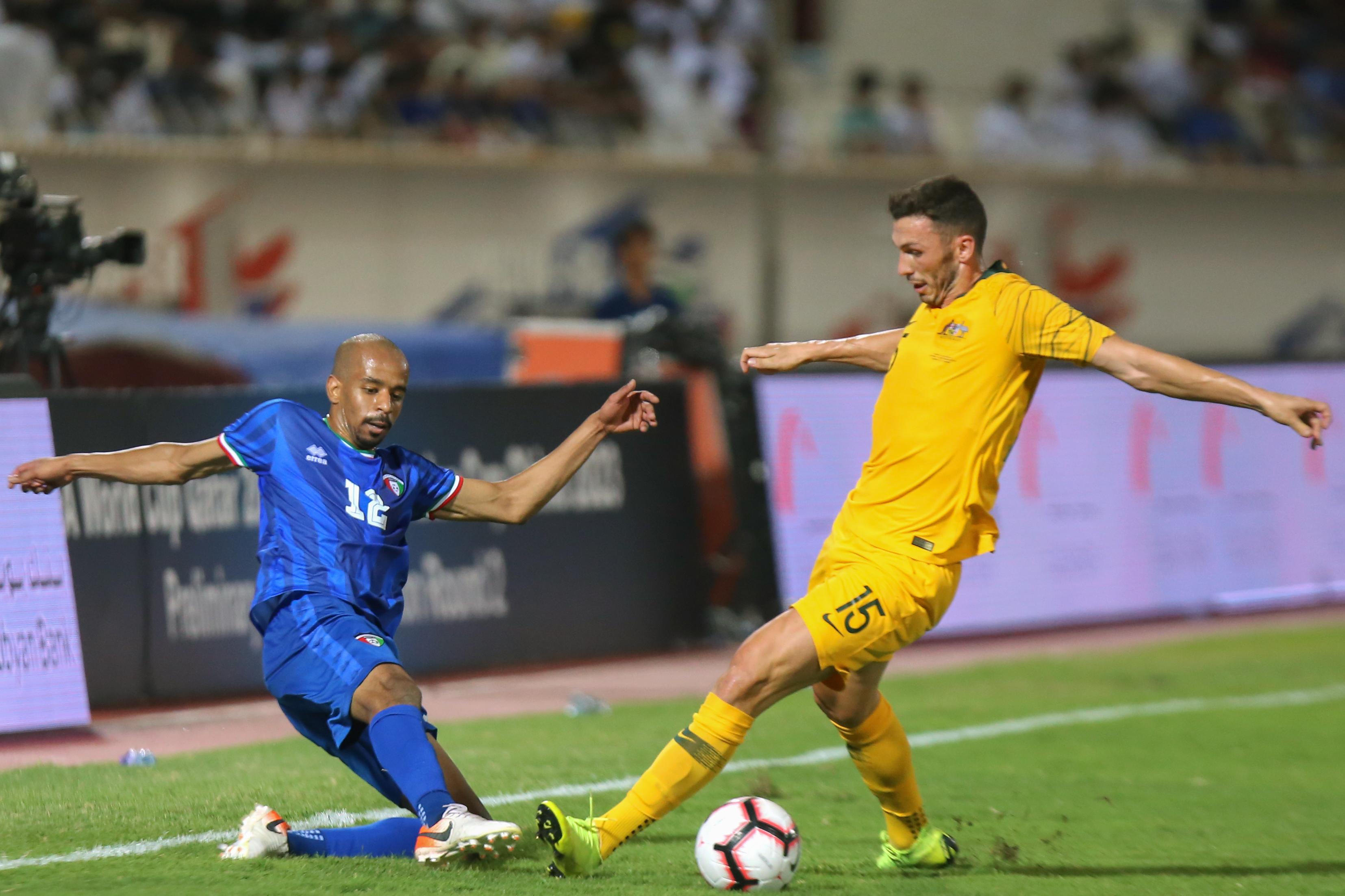 اللاعب الكويتي حمد الحربي يحاول إيقاف مهاجم أستراليا