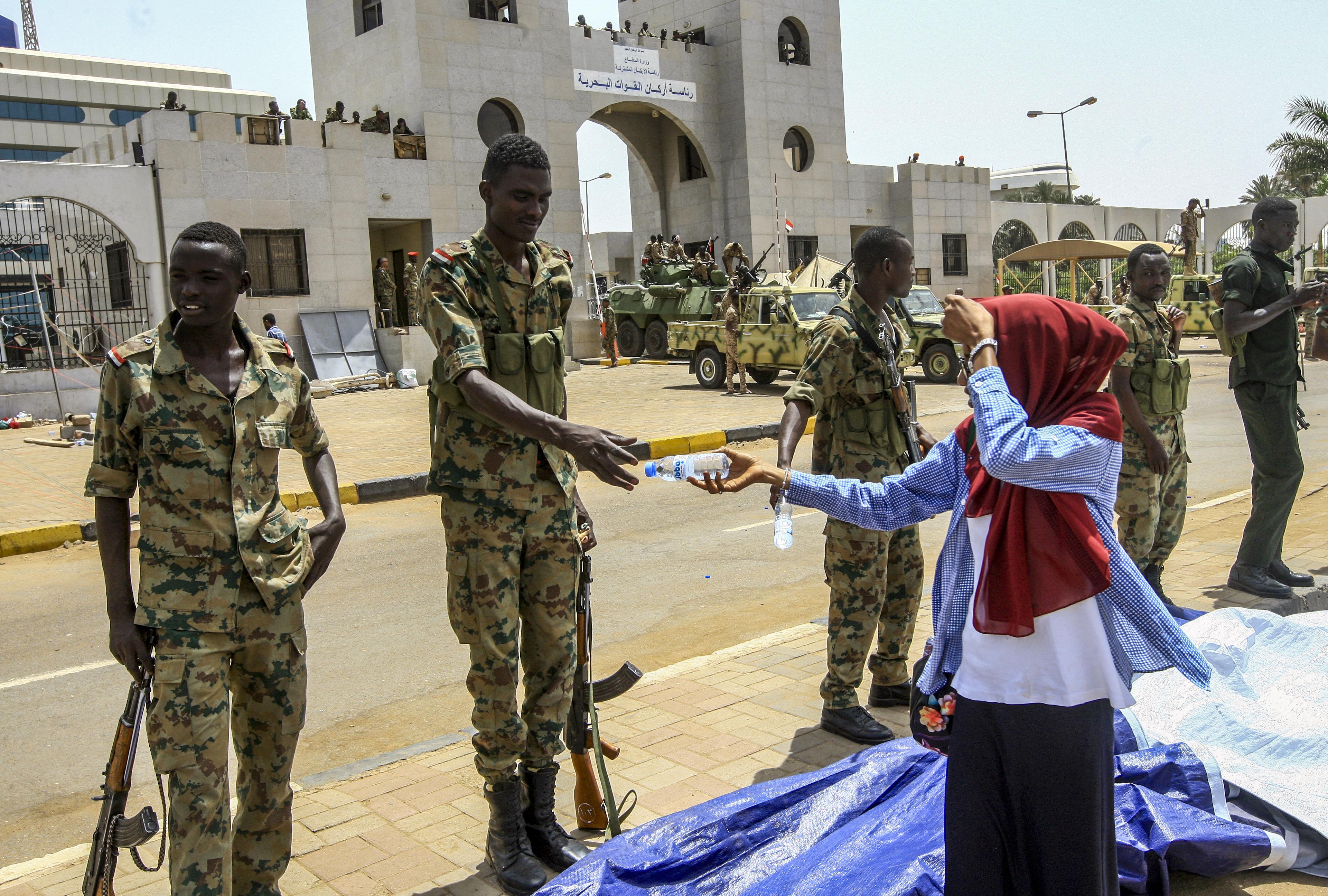 امرأة تناول جنديا سودانيا قنينة ماء عقب تظاهرات ضد تسلم العسكر الحكم في البلاد