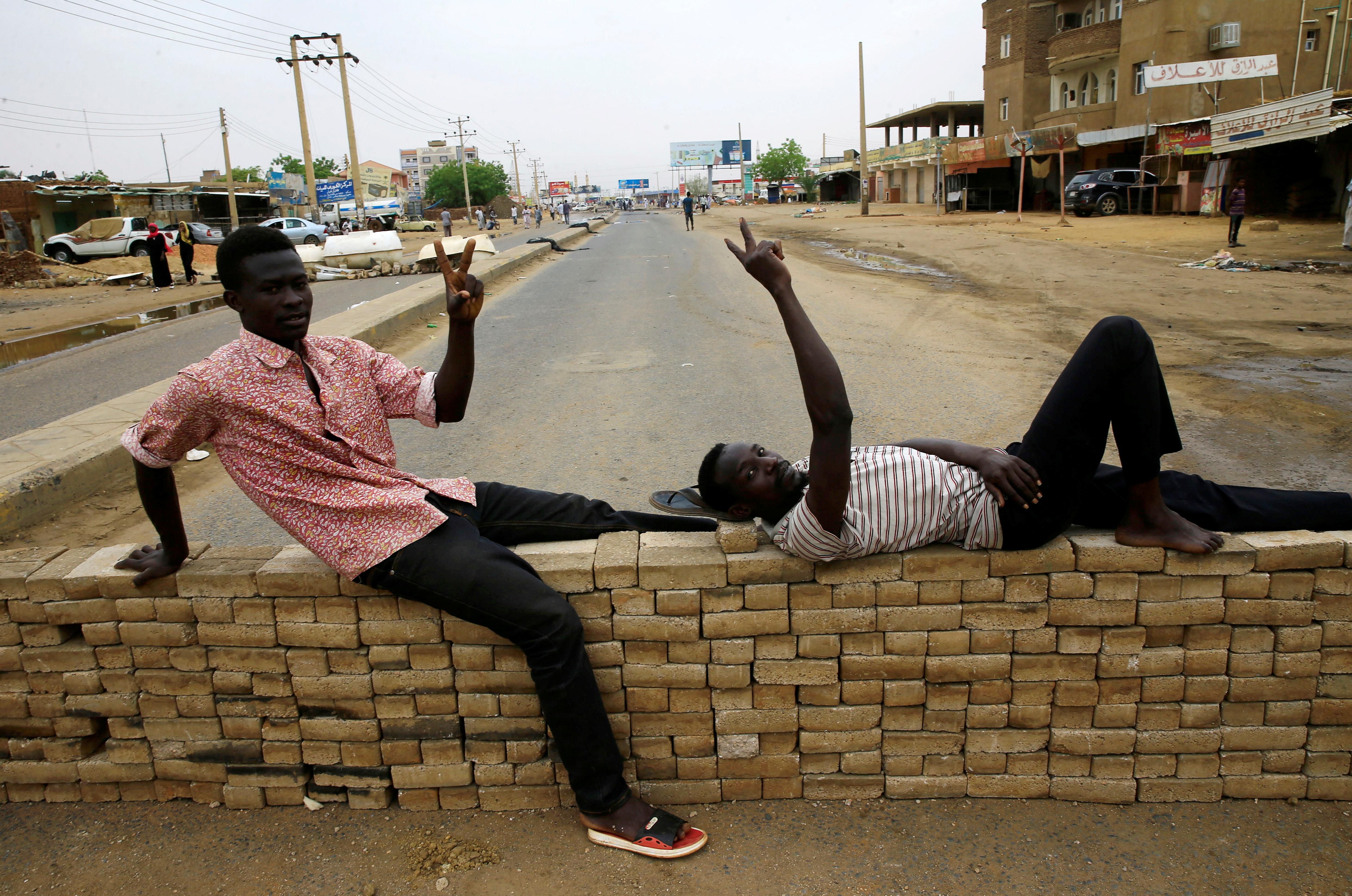 سودانيان يقفان عند حاجز شيده المحتجون في يوم العصيان المدني بالخرطوم