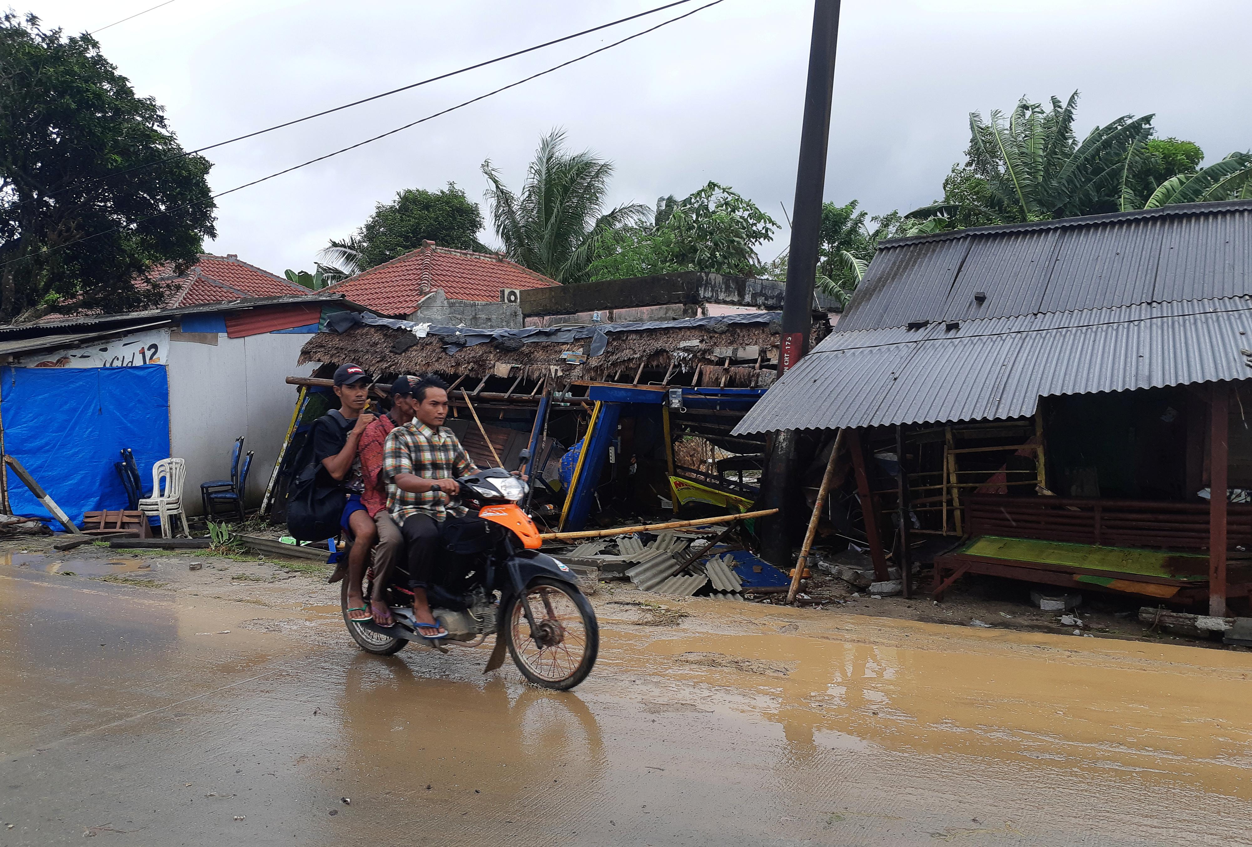 مواطنان يسيران على دراجة نارية بالقرب من الدمار الذي حل بمدينتهم جراء تسونامي