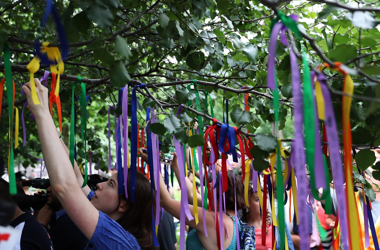 أميركيون يعلقون الأشرطة الملونة على أغصان الشجرة الناجية في نيويورك تكريما لأرواح ضحايا هجوم أورلاندو في حزيران/يونيو 2016