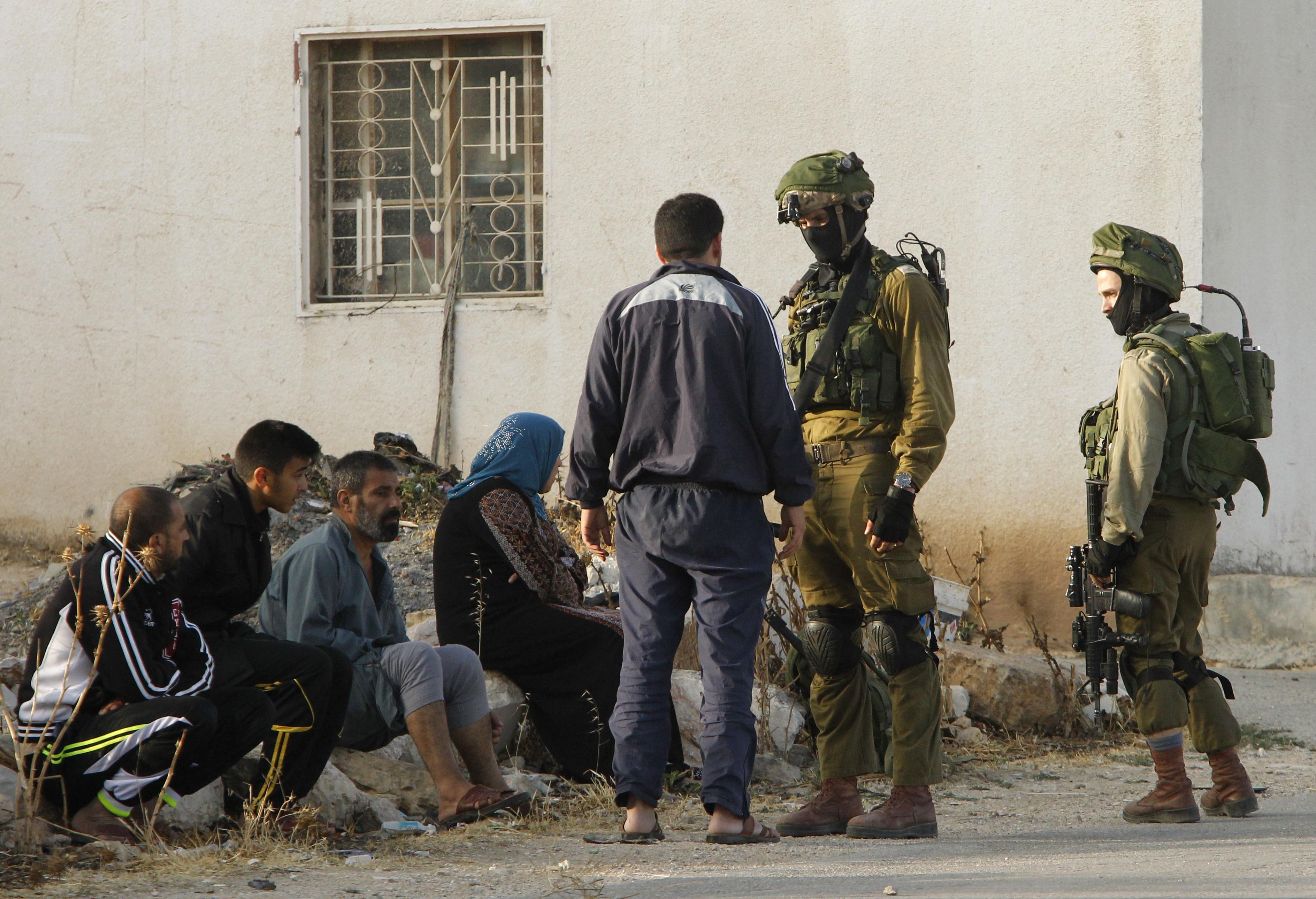 جنود إسرائيليون يتحدثون إلى فلسطينيين في بلدة يطا التي يسكنها منفذا هجوم تل أبيب