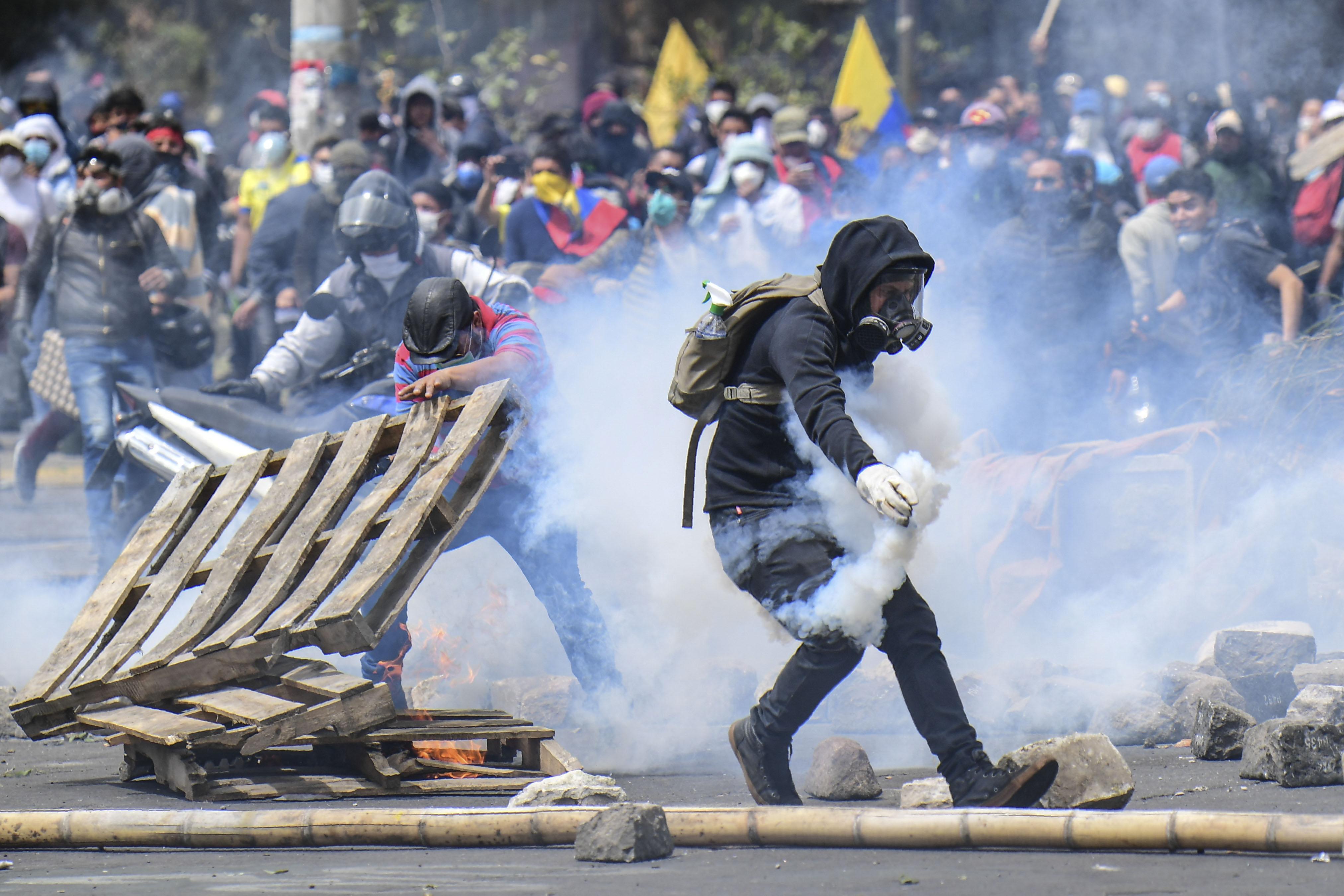 متظاهر يرتدي قناع غاز بالإكوادور يتعامل مع إحدى قنابل العاز المسيلة للدموع - 11 أكتوبر 2019