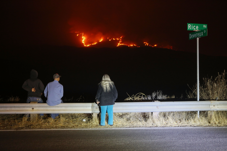مواطنون يشاهدون من على أحد الطرق حريق توماس وهو ينر بالجبال في مدينة أوجاي بكاليفورنيا