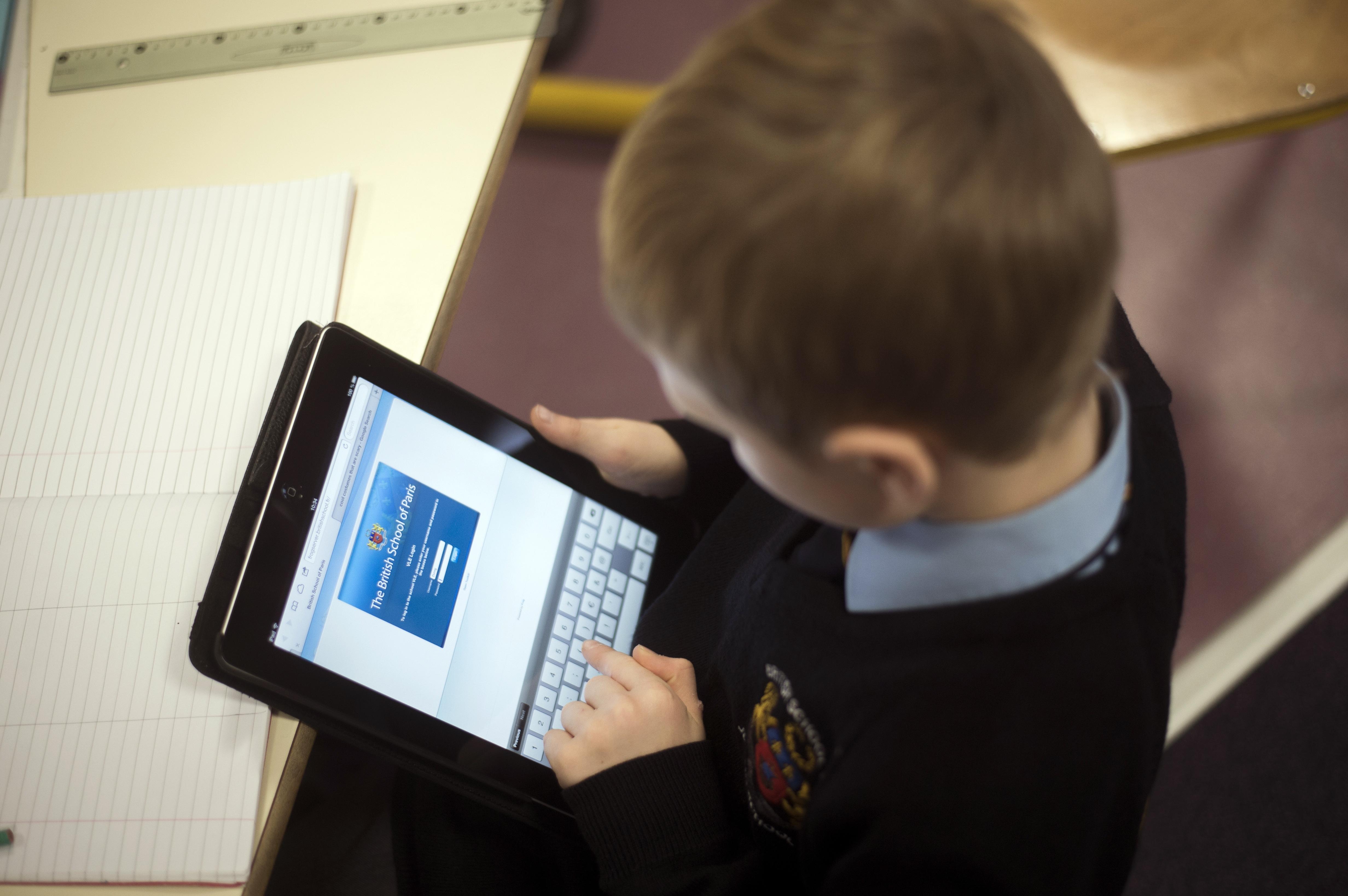 طفل يستخدم جهاز آيباد اللوحي