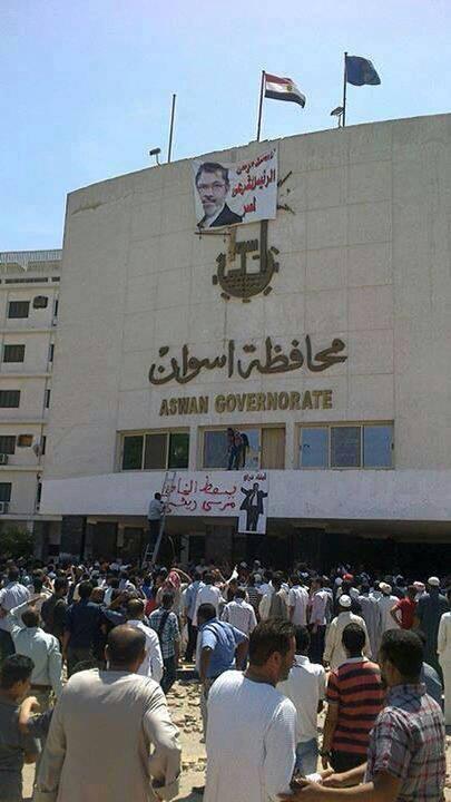 متظاهرون يضعون صورة للرئيس المصري المعزول محمد مرسي على مبنى محافظة أسوان