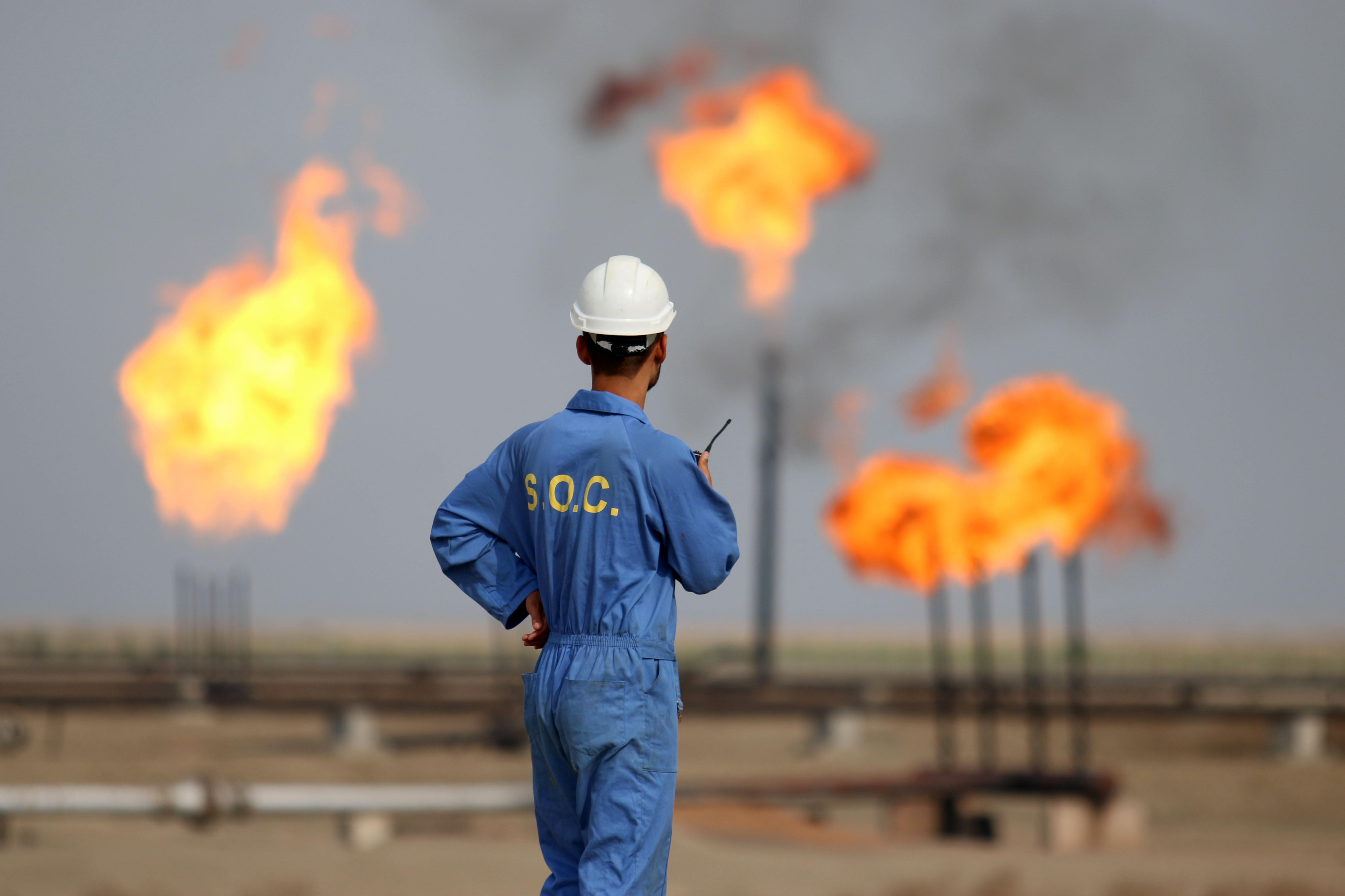 عامل أمام إحدى مصافي النفط جنوبي العراق