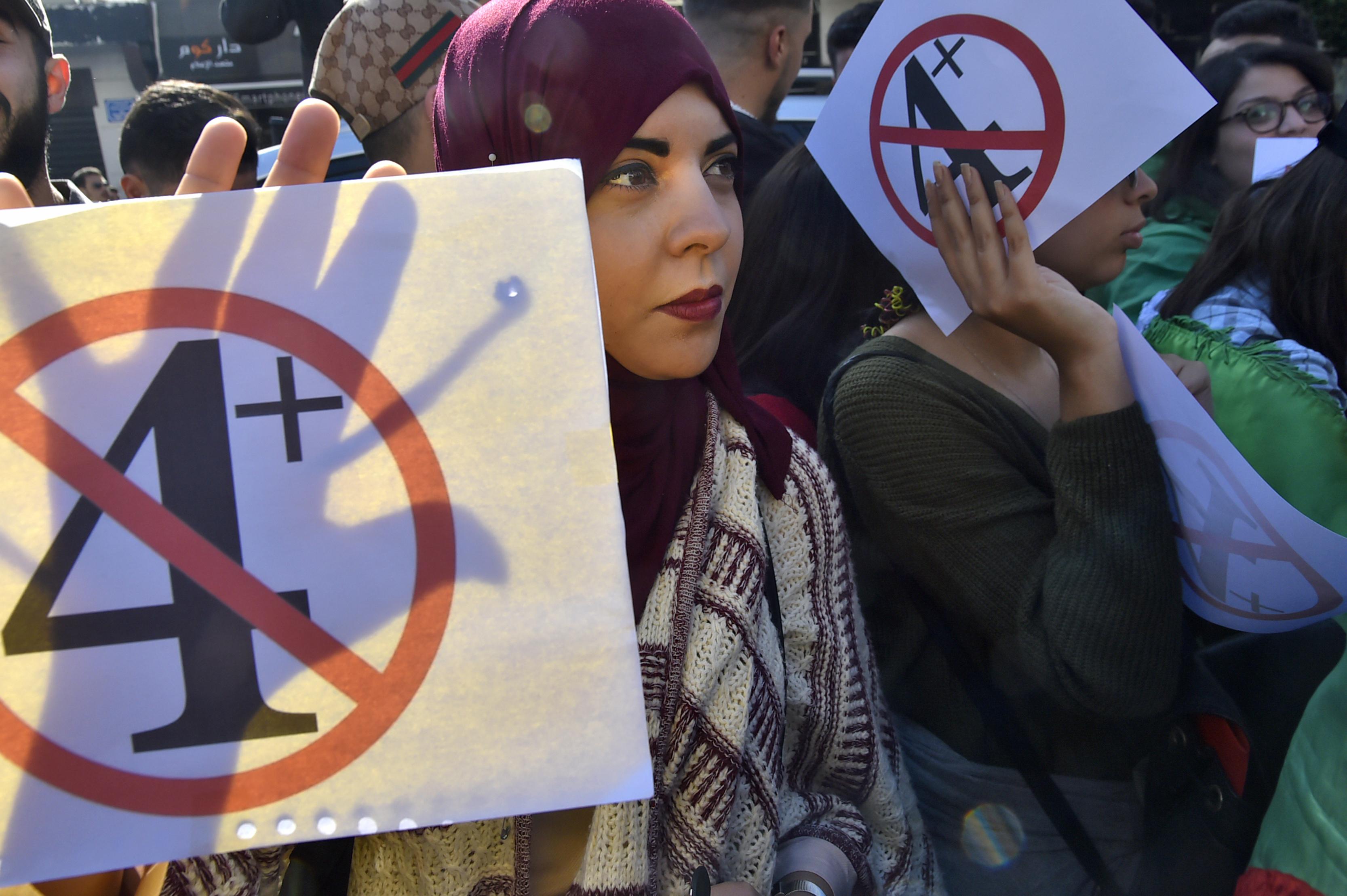 جزائرية تحمل لافتة تعبر عن رفض قرار بوتفليقة عدم الترشح والبقاء في منصبه فترة غير محددة