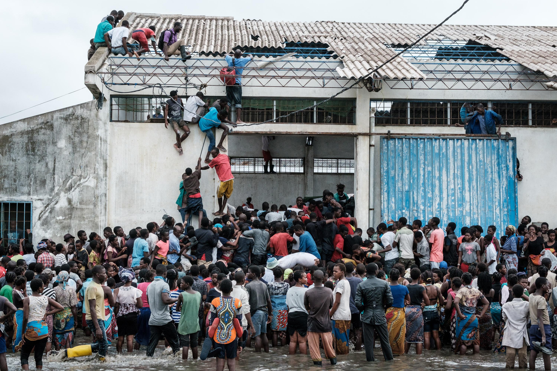 مواطنون من موزمبيق بانتظار أكياس الأرز أمام مستودع للمساعدات