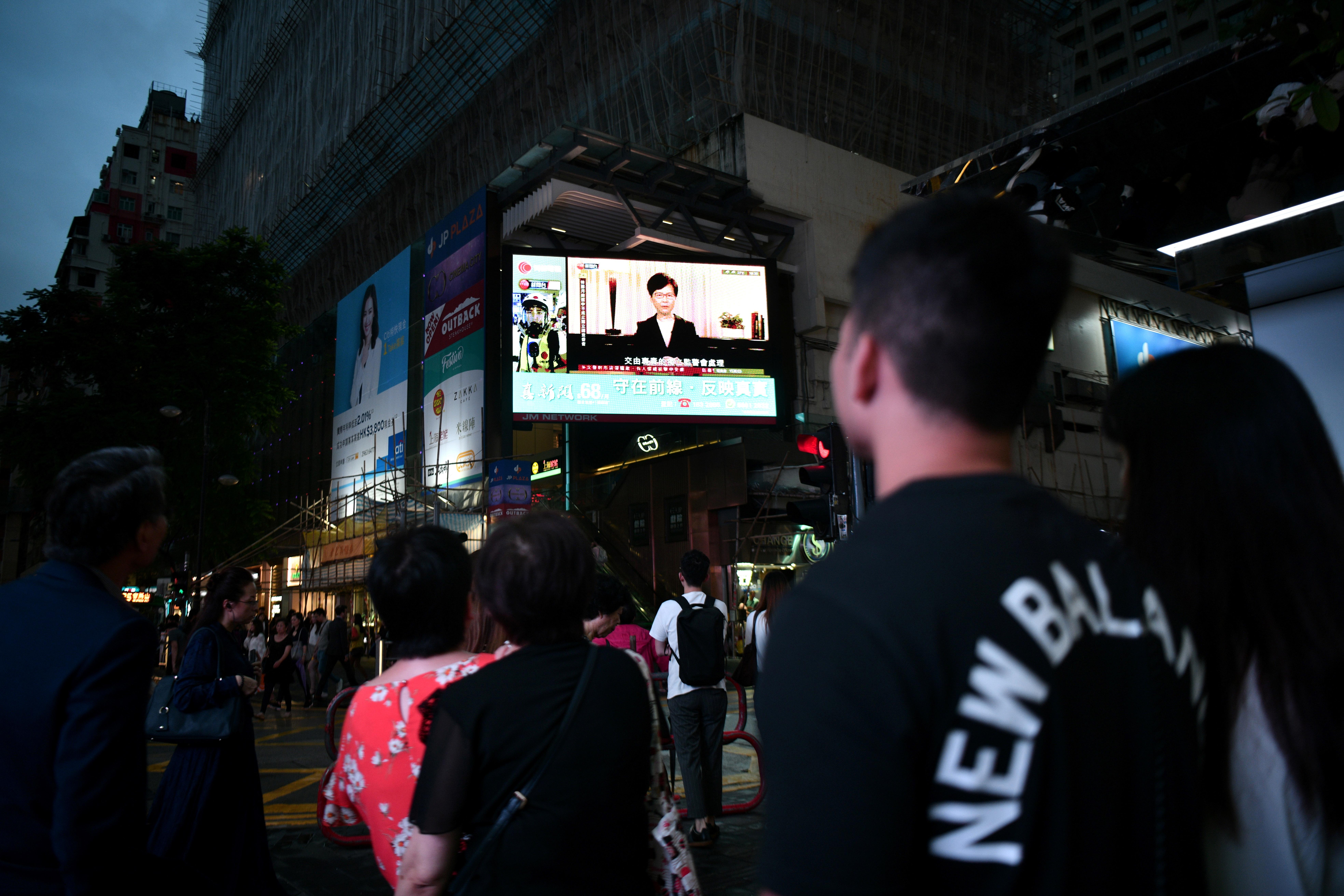 مشاة في هونغ كونغ يشاهدون خطاب رئيسة السلطة التنفيذية في هونغ كونغ كاري لام - 4 سبتمبر 2019
