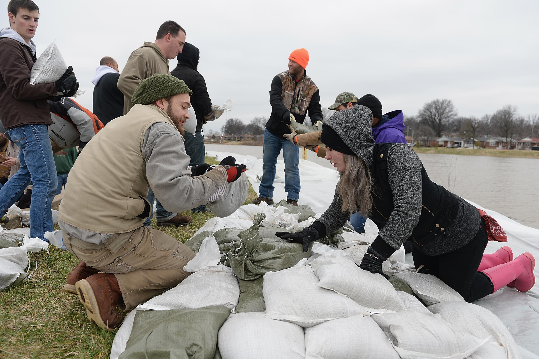 متطوعون يضعون أكياس الرمل على ضفاف أحد الأنهار في ميزوري