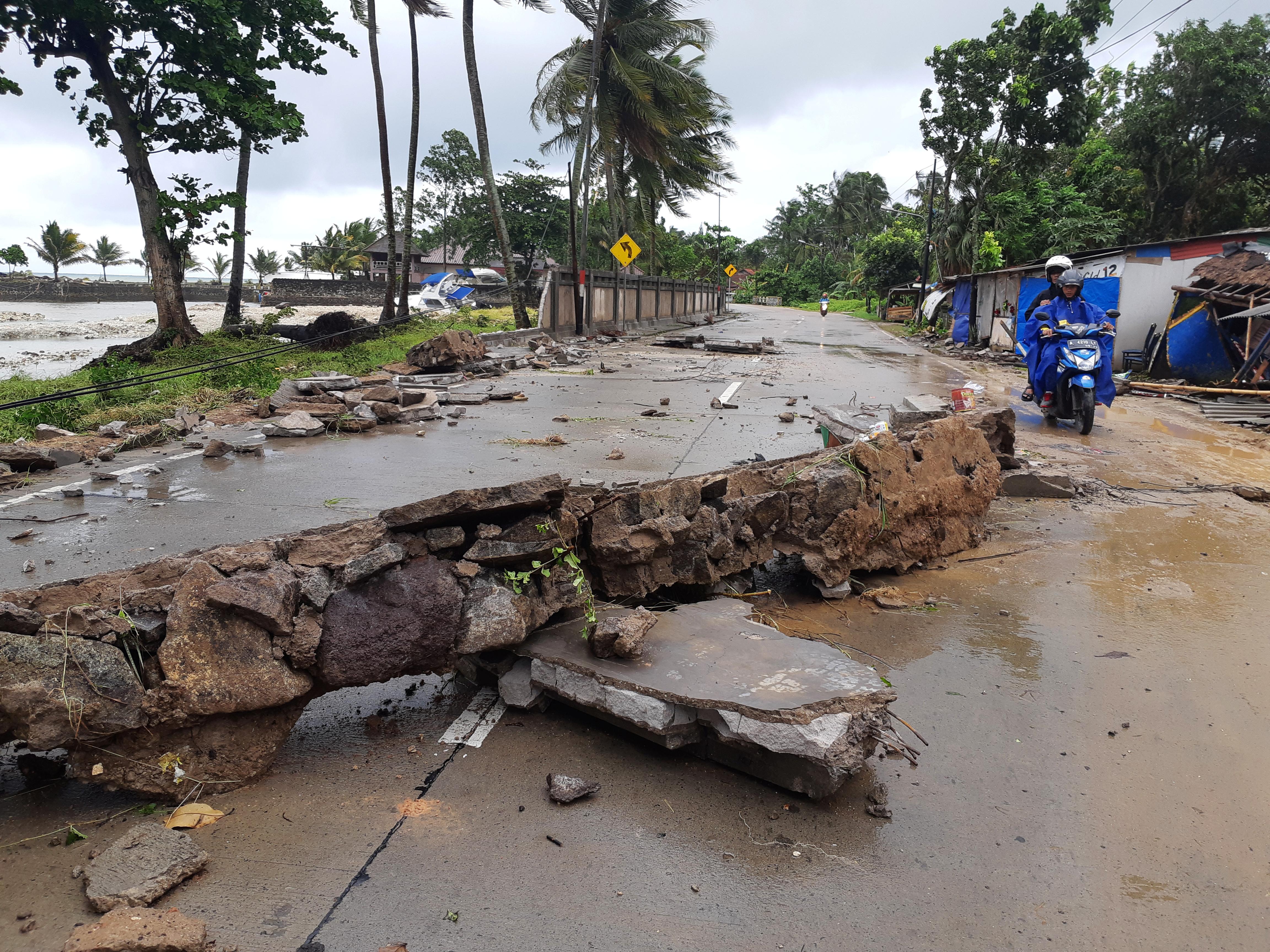 مواطن يسير على أرض تضررت بسبب تسونامي