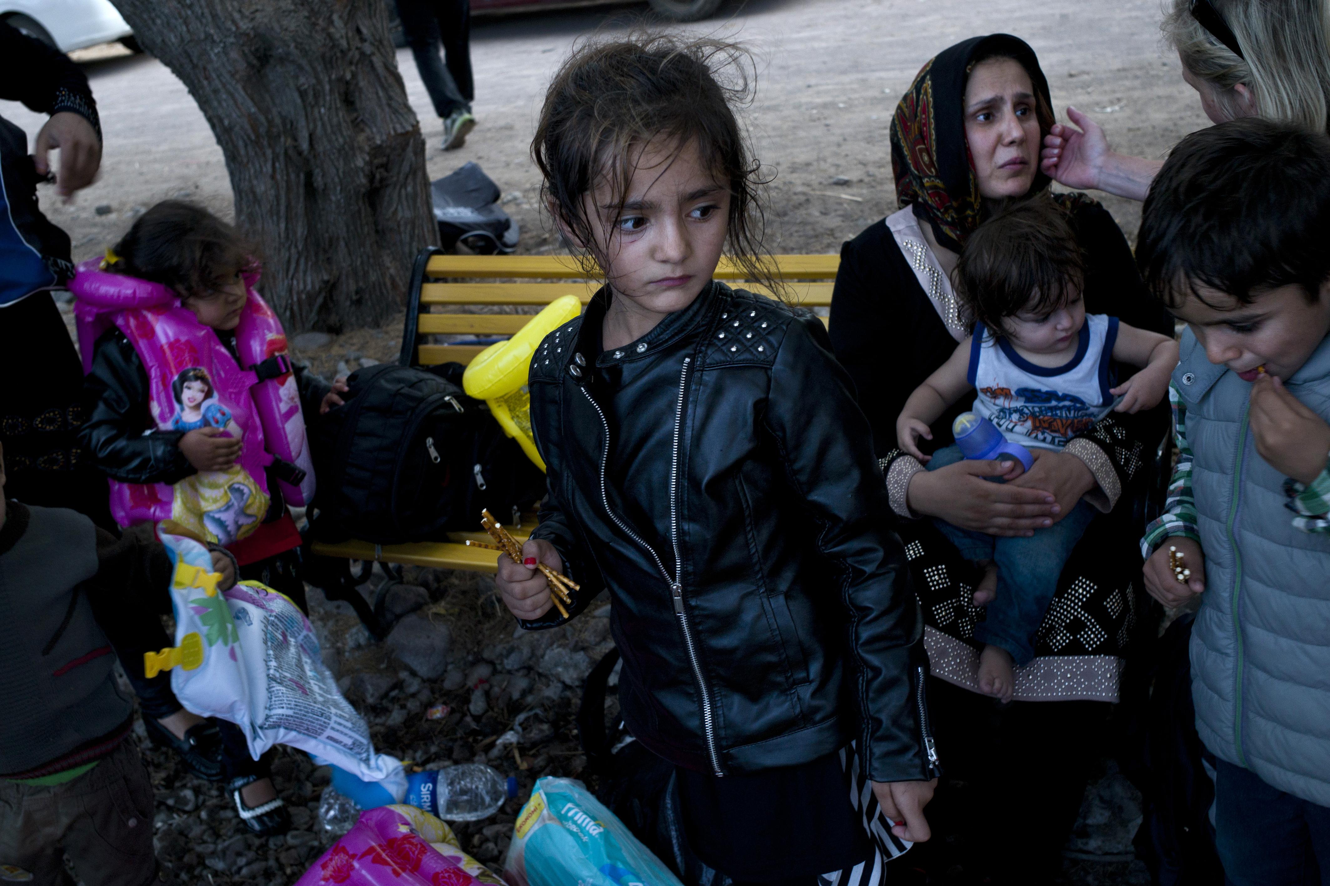 مهاجرون ينتظرون على الشاطئ بعد وصولهم إلى جزيرة ليسبوس اليونانية بعد عبور بحر إيجة من تركيا